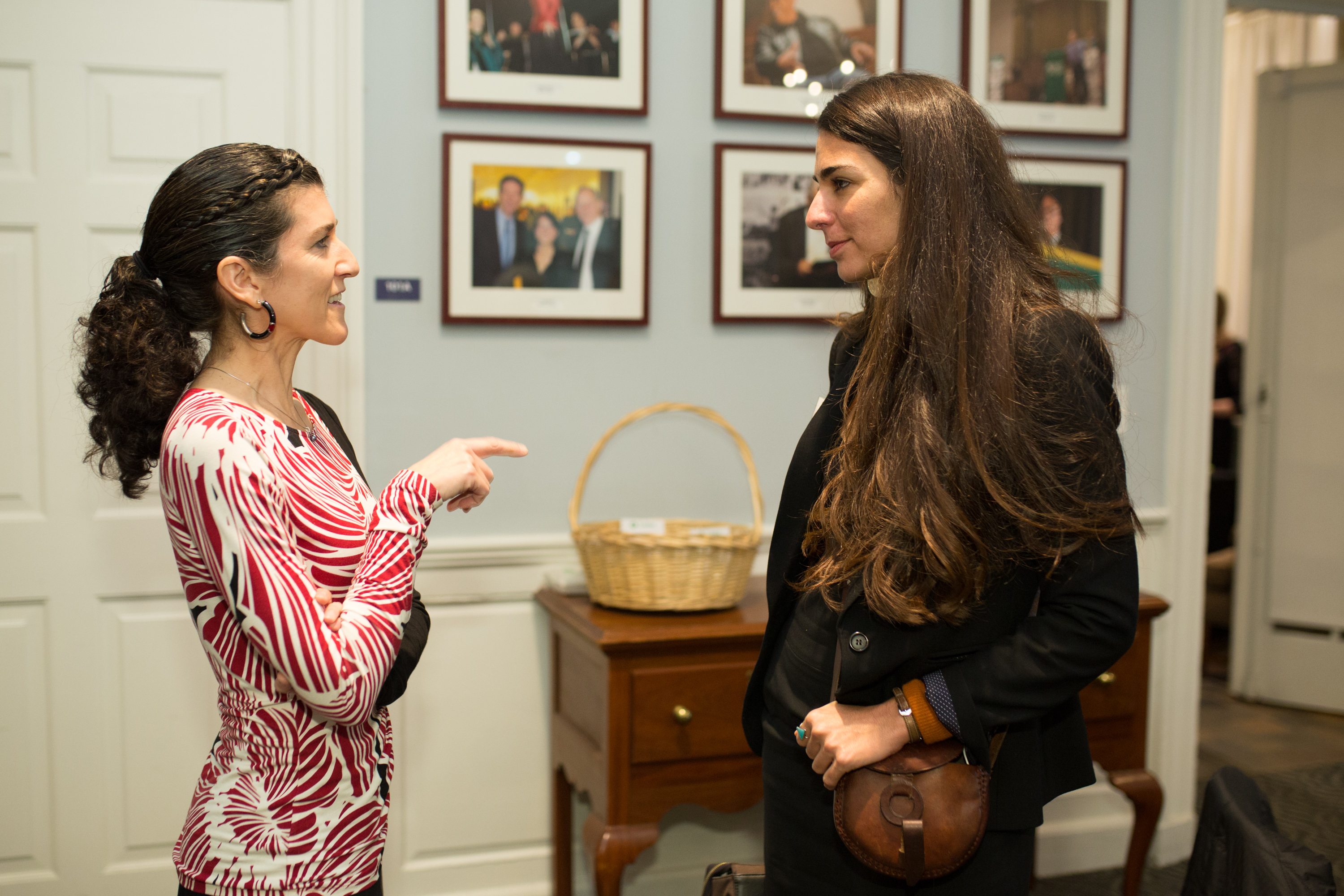 Lisa Fiore in a red and white dress stands and talks face-to-face with Saameh Solaimanim, who is dressed in black