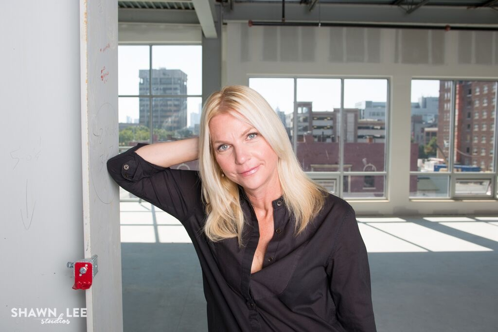 Photograph of new College of Art and Design Dean Amy Green Deines leaning up against a wall.
