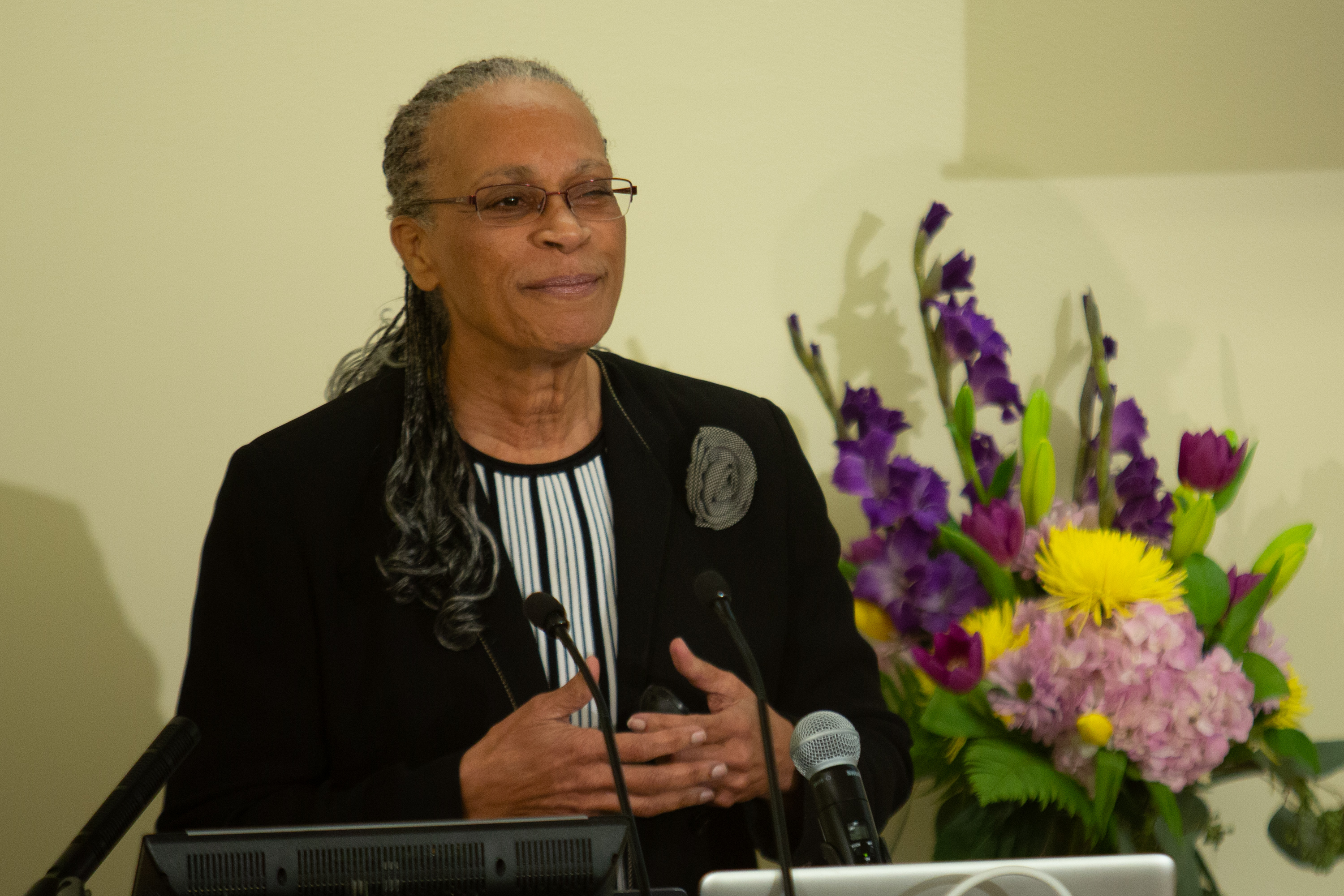 Dr. Arnetha Ball speaks at the podium with a bouquet of flowers in the background.