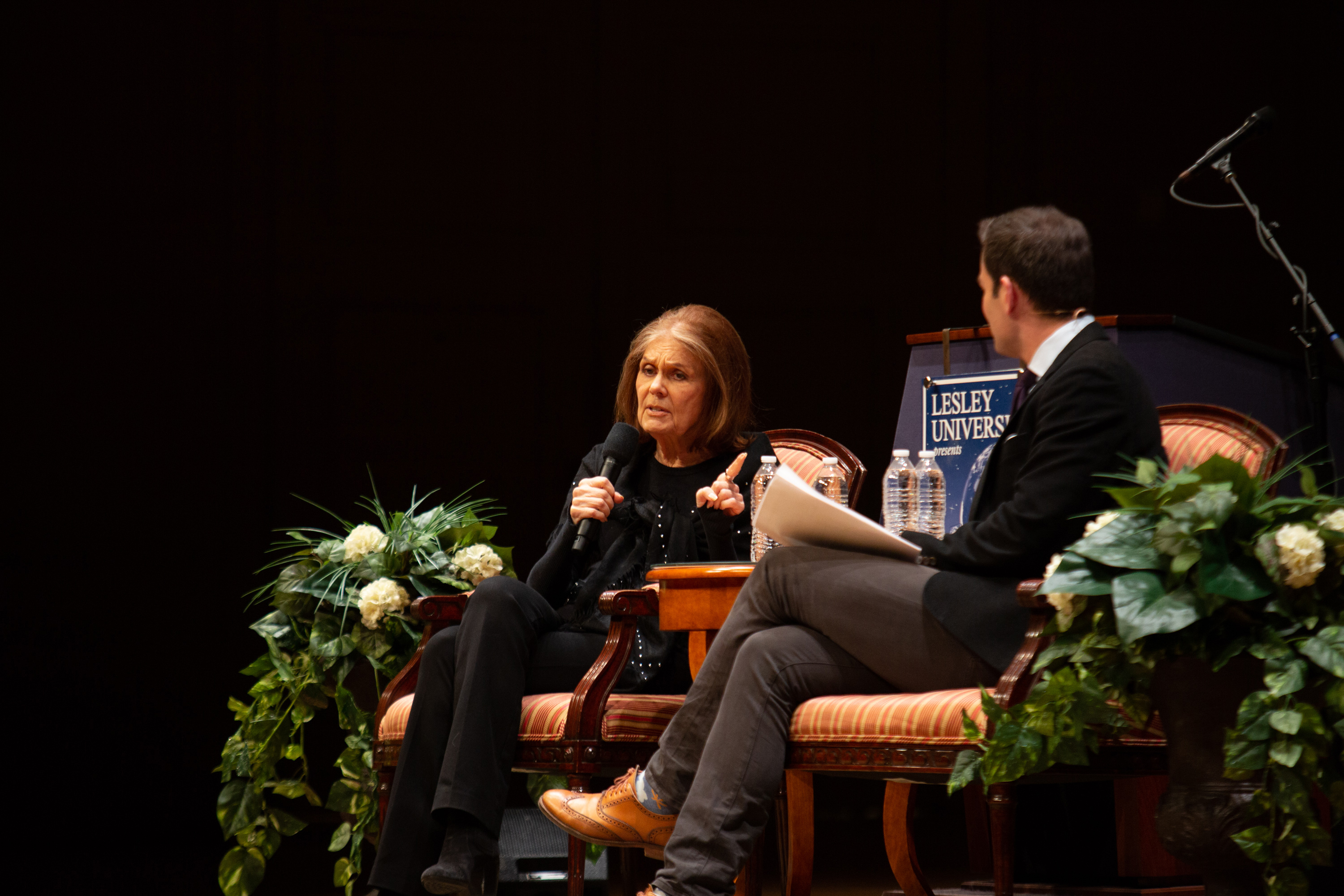 Gloria Steinem talks while seated next to Jared Bowen