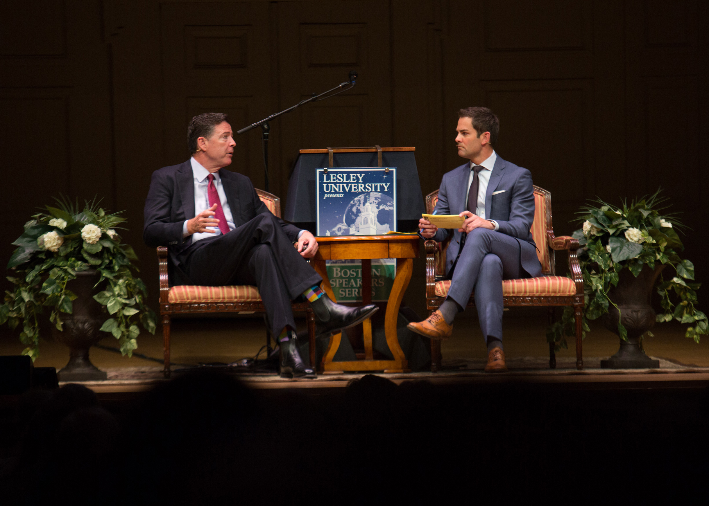 James Comey and Jared Bowen seats on the Symphony Hall stage