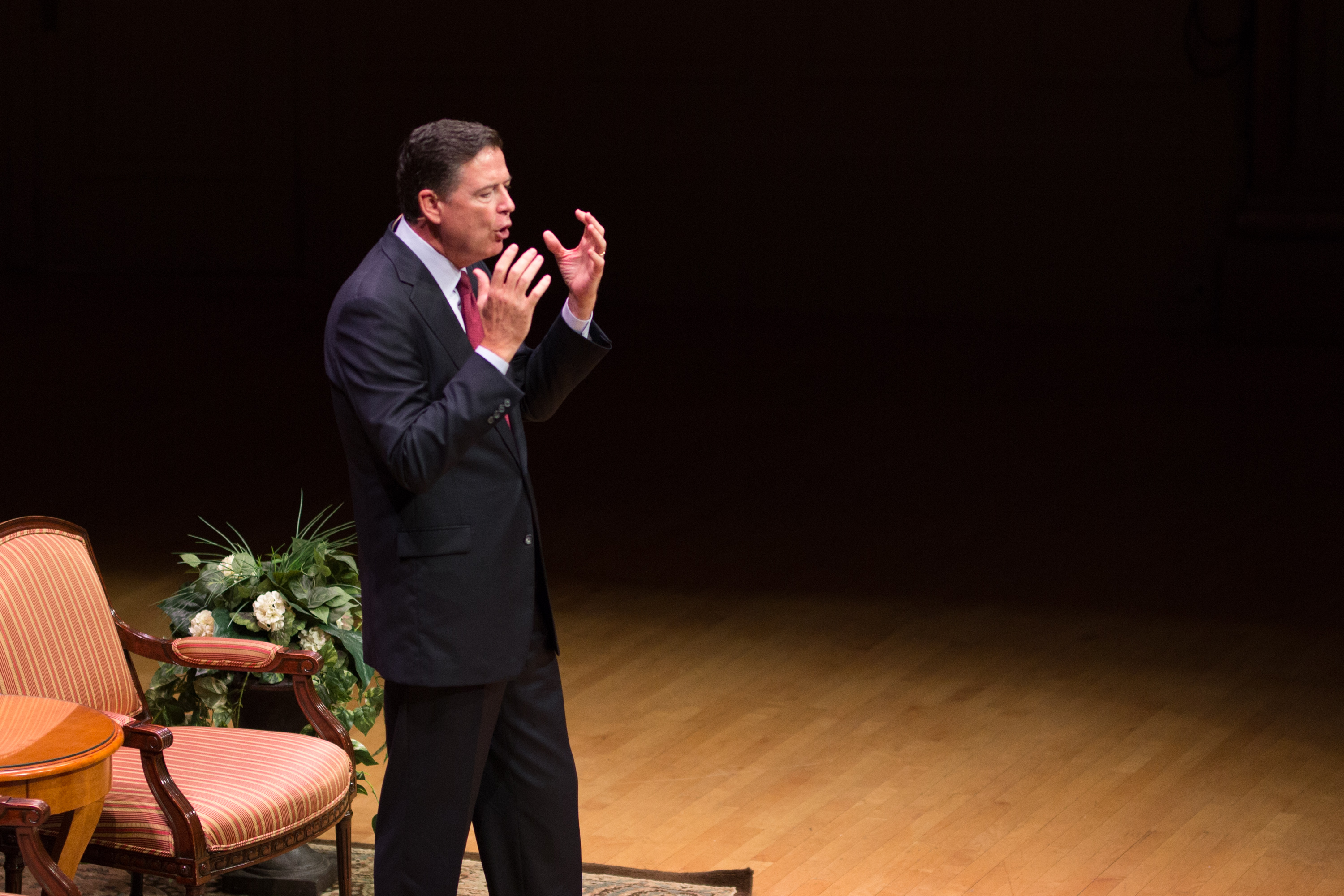 James Comey gestures with both hands while speaking on the Symphony Hall stage