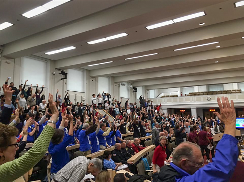 Massachusetts legislators raise their hands to show support after McMillan speaks on behalf of Teens Leading the Way.
