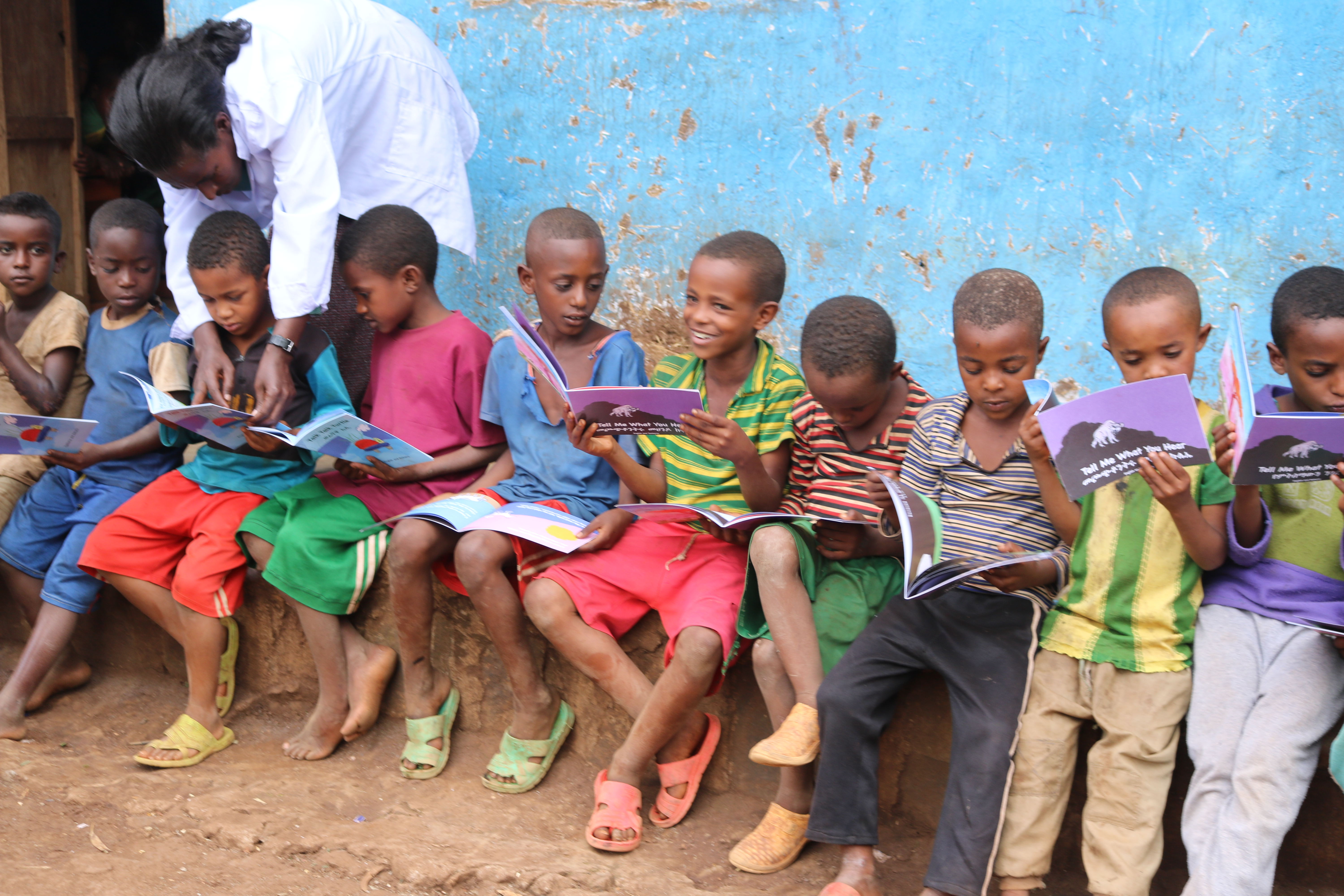 Children sitting outside on a sidewalk in Ethiopia with their science books.