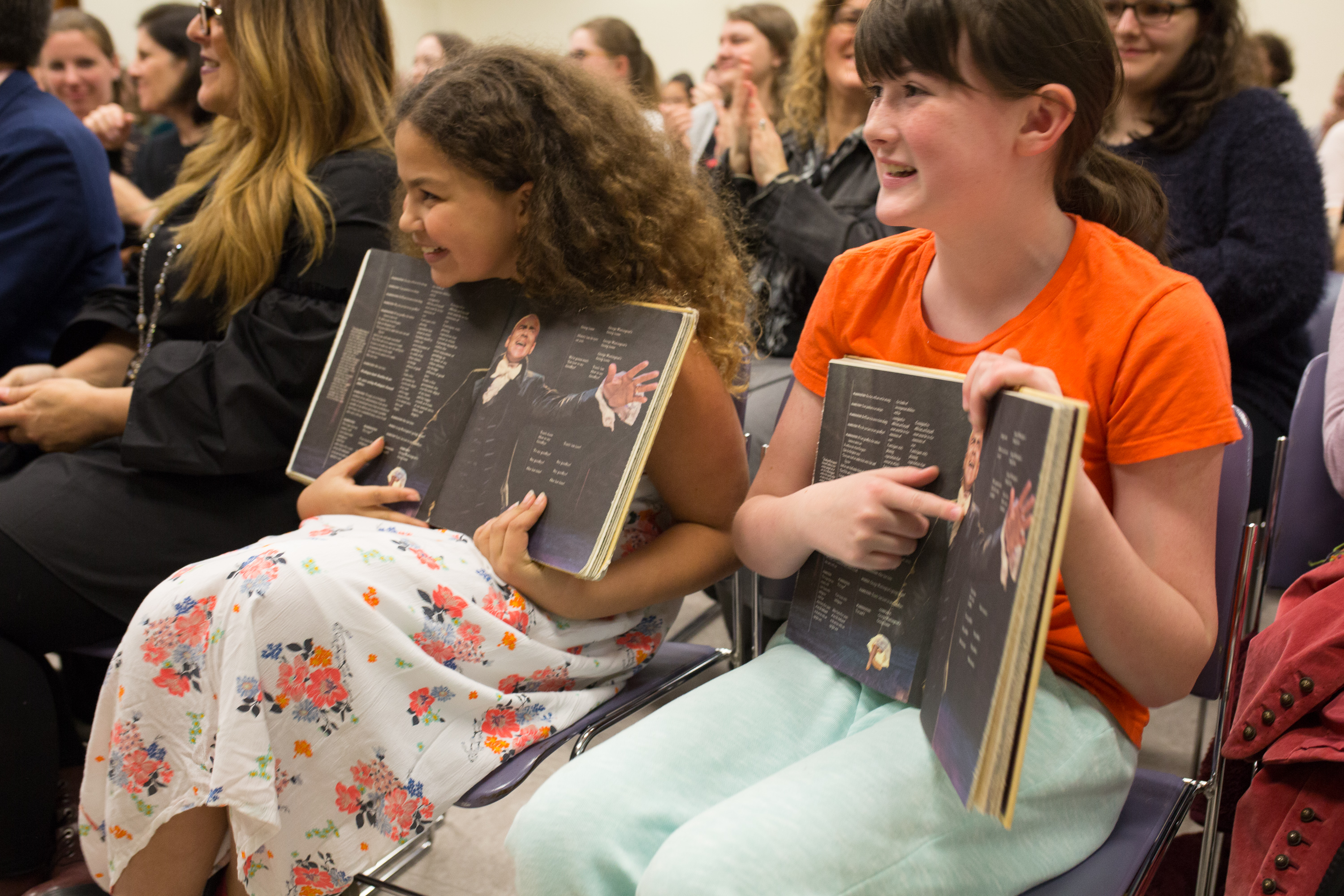 "Two young girls hold open a page of the ""Hamilton"" book with Christopher Jackson's picture."