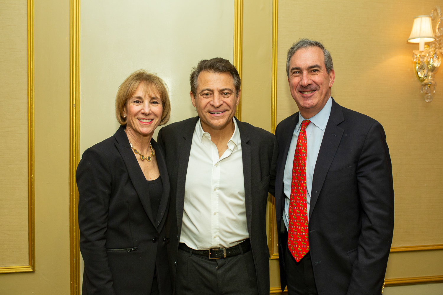A man and woman stand on either side of Peter Diamandis