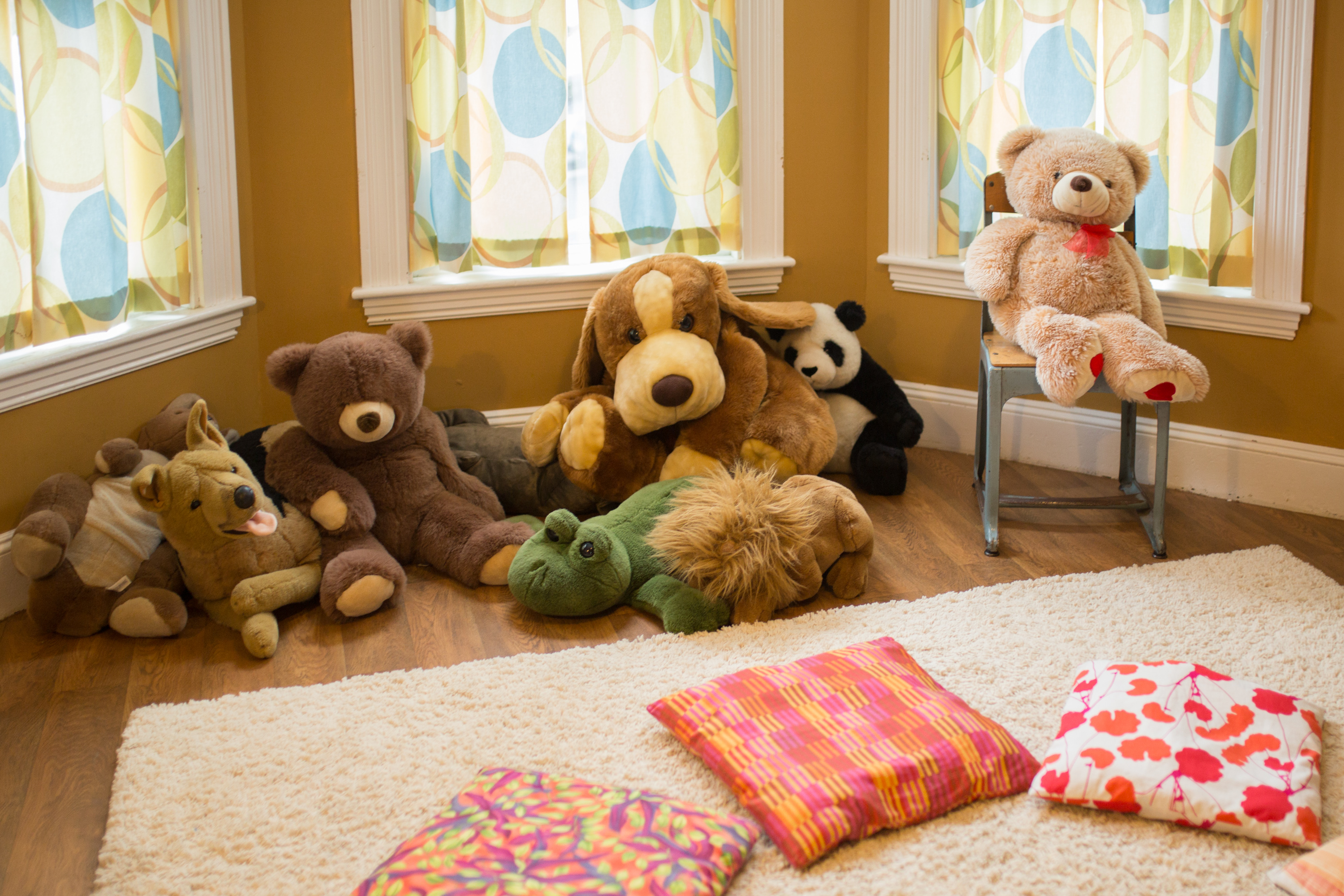 A room with teddy bears and floor pillows.