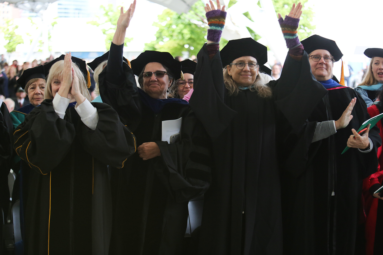 Faculty clap and raise their hands in celebration at Commencement.