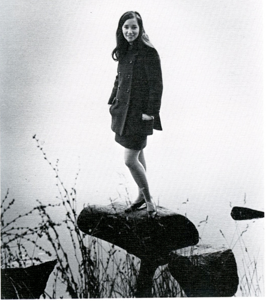 Debbie Schwartz poses for a photo on a rock surrounded by water.