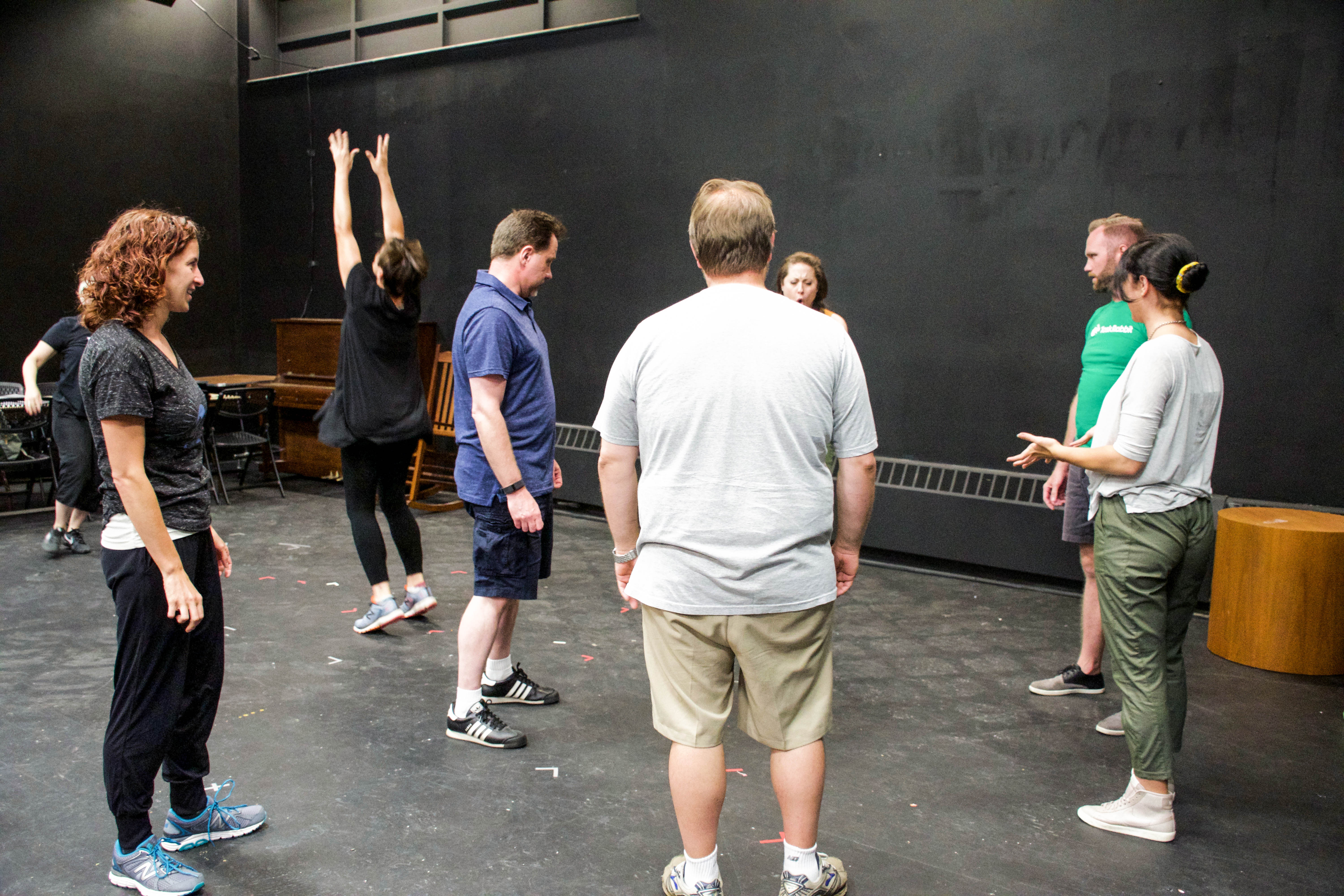 Actors in a rehearsal room standing in a circle working on movement