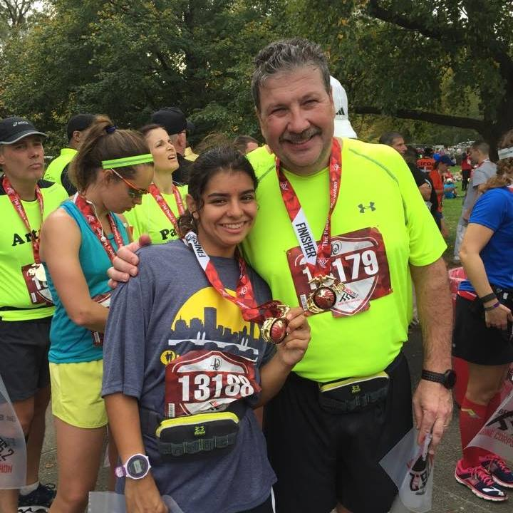 Hanna and her father John Adams wearing race medals after the Marine Corp Marathon