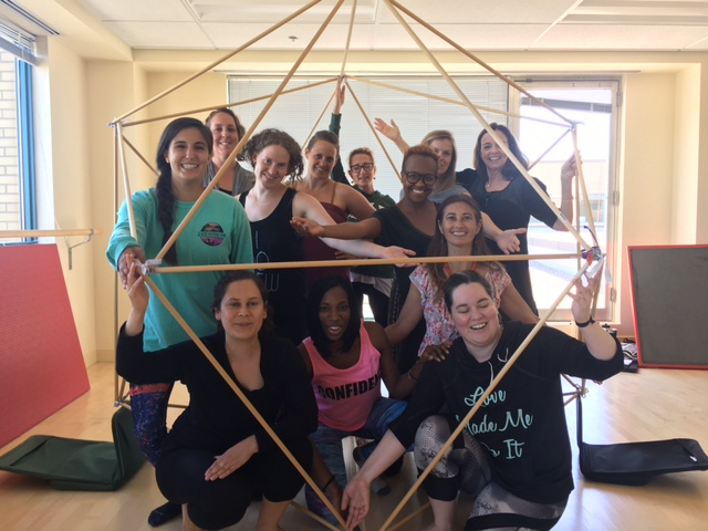 Students pose inside a hexahedron-shaped structure.