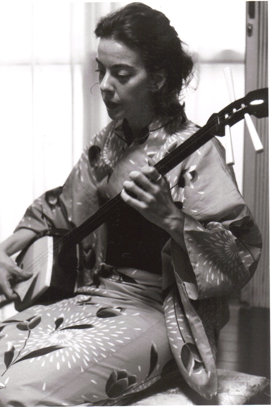 Janet Pocorobba plays the shamisen in a traditional Japanese dress. The shamisen is a three-stringed instrument with a long neck like a guitar.