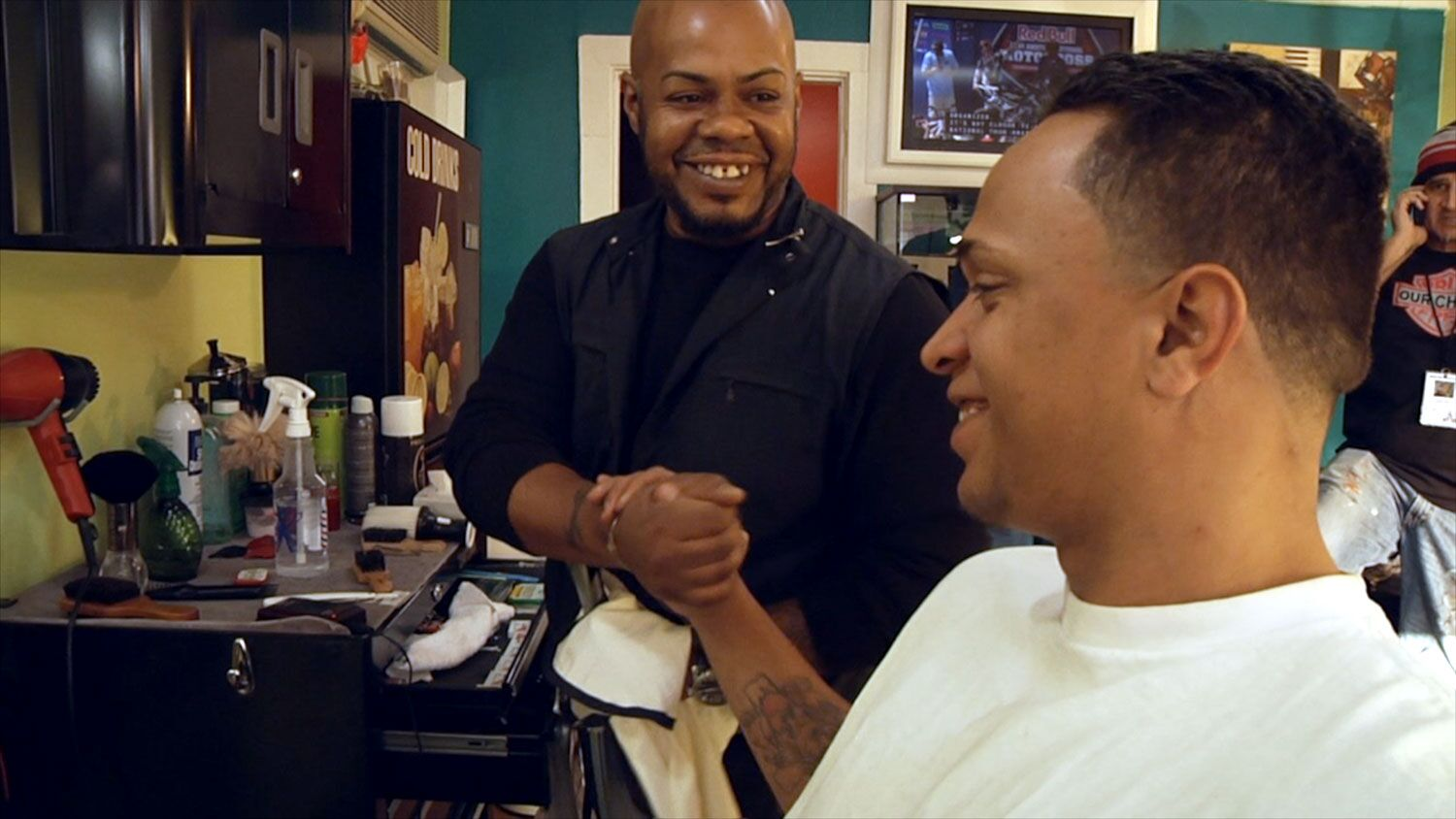Billy Cabrera shakes hands with Jesus Ruiz in the barber shop.