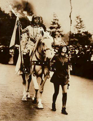 A sepia toned image of a woman dressed as Joan of Arc rides a horse lead by another woman.