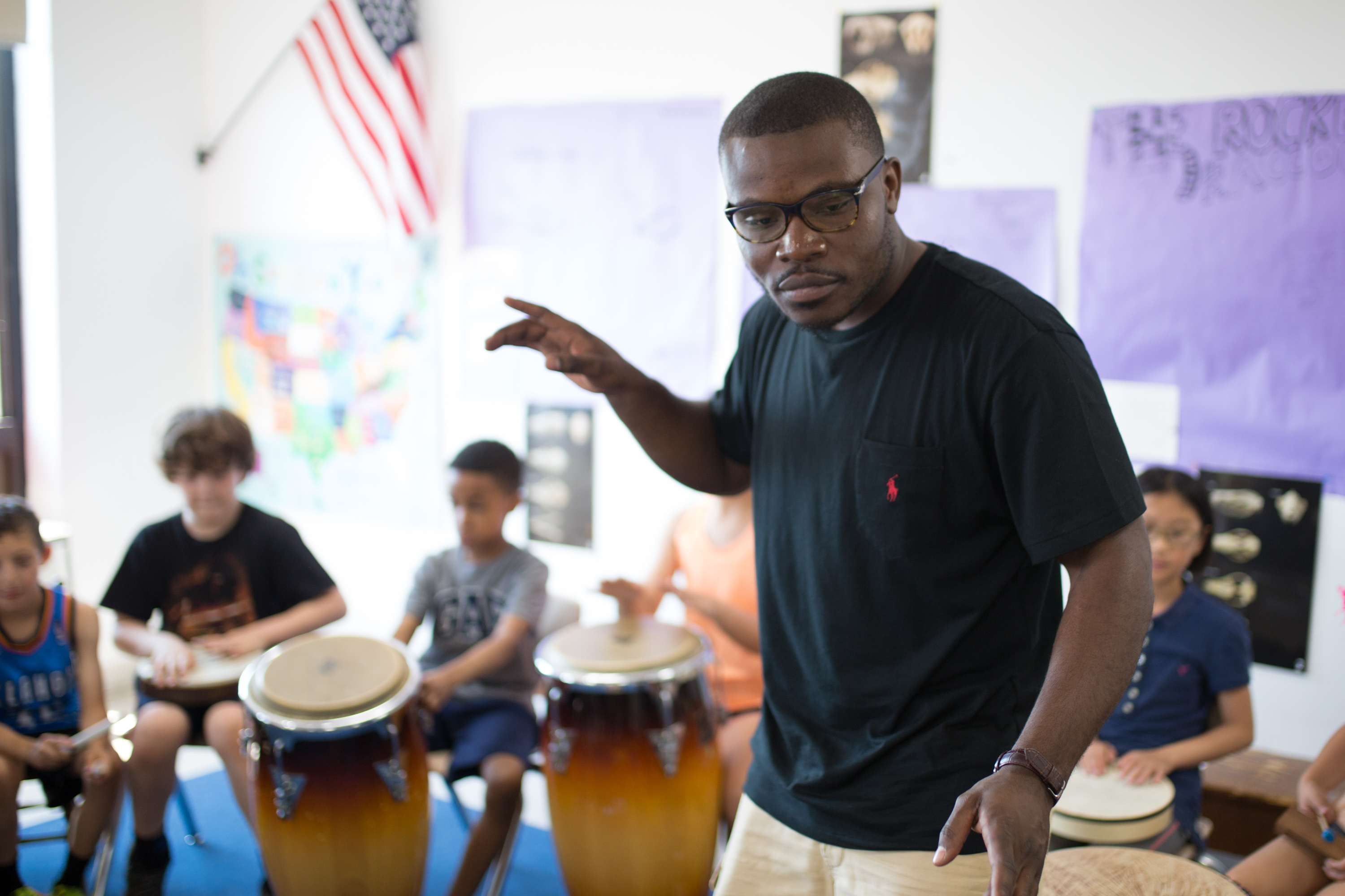 Jonathan Mande teaching a drum class with young children in a circle around him, each child holding a drum
