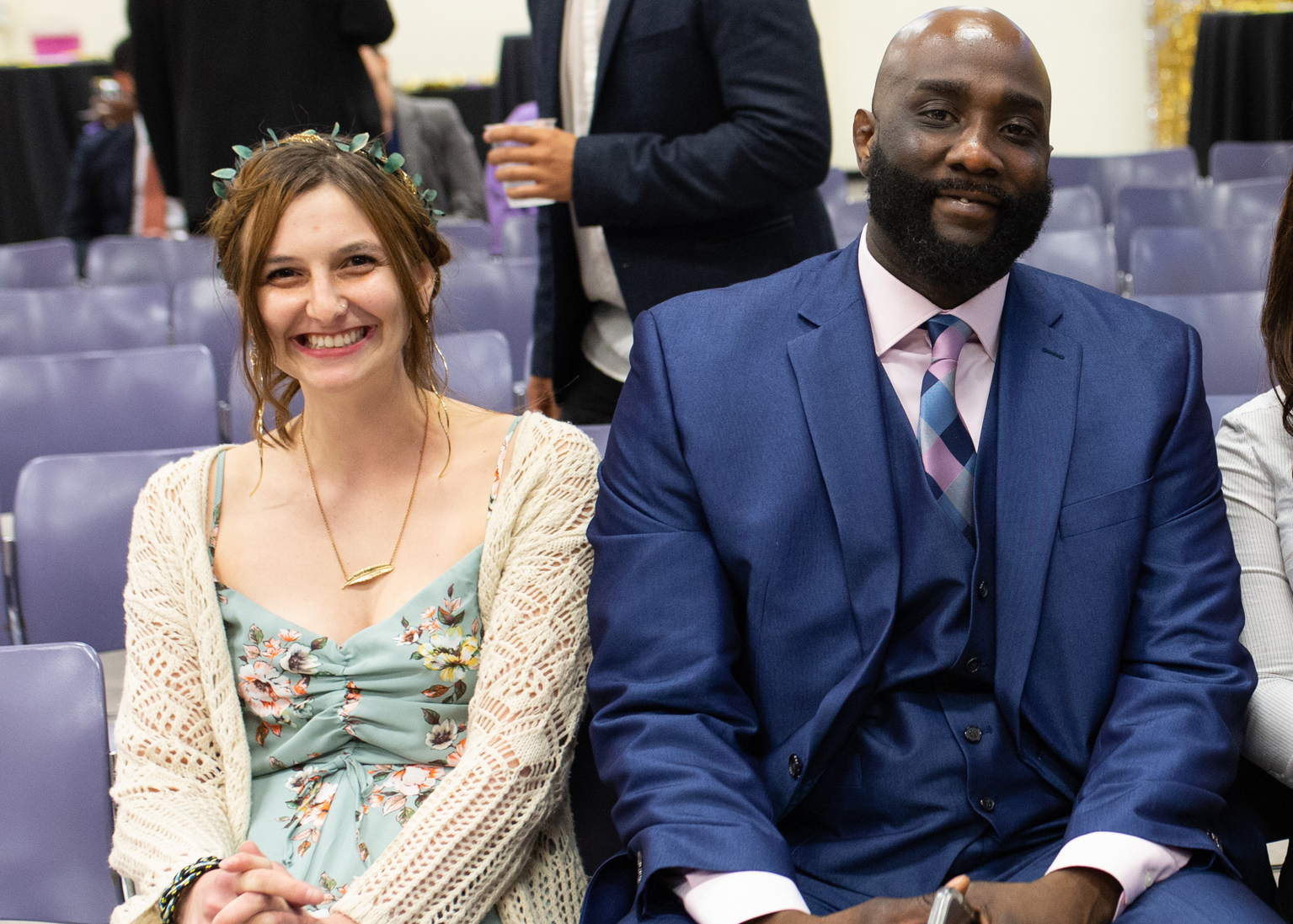 Katya Zinn and Tyrell Dortch are seated next to each other and smiling at the camera.