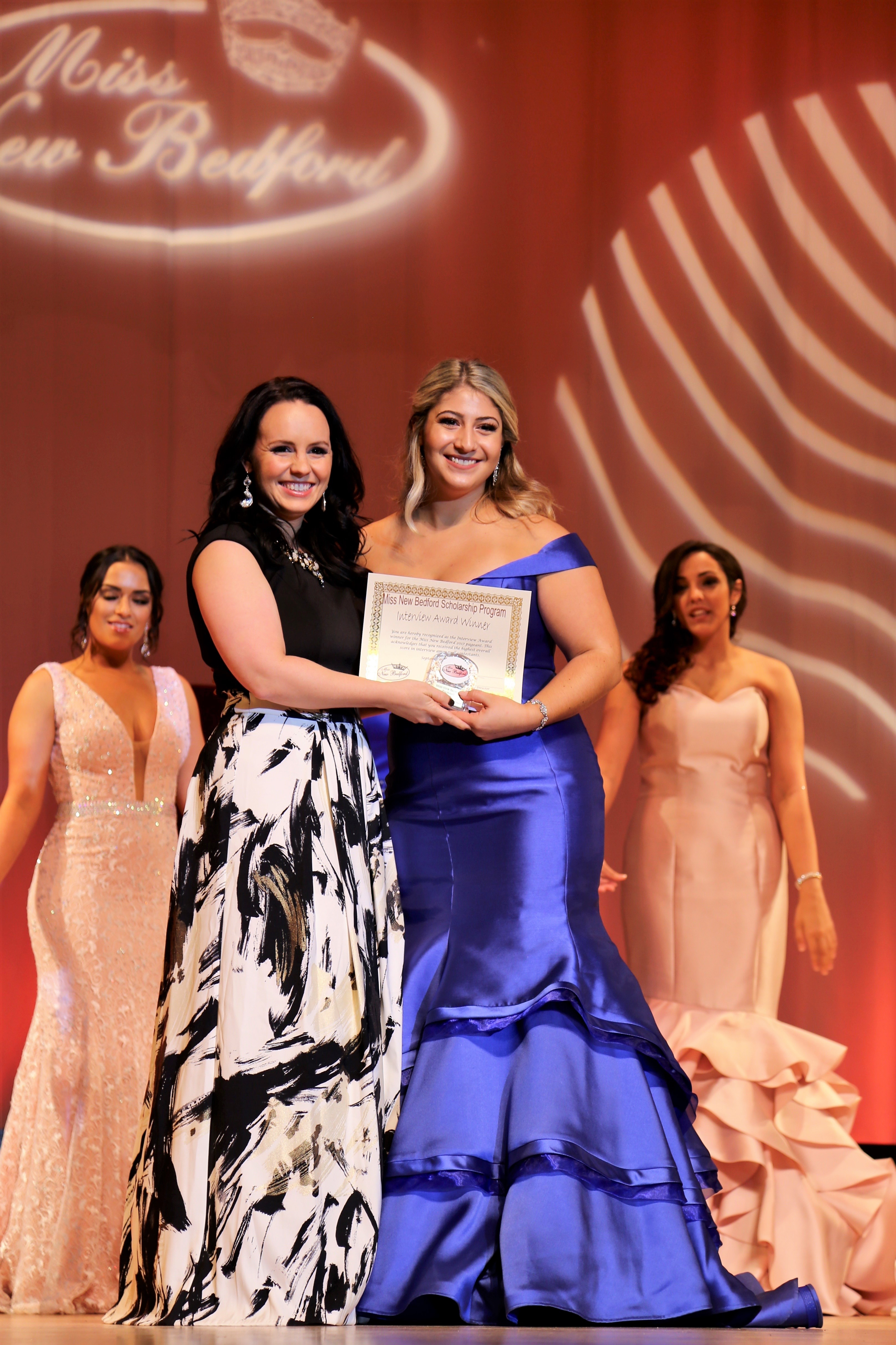 Kenzie Moniz receives the Interview Award standing on stage in a floor-length shiny purple dress.