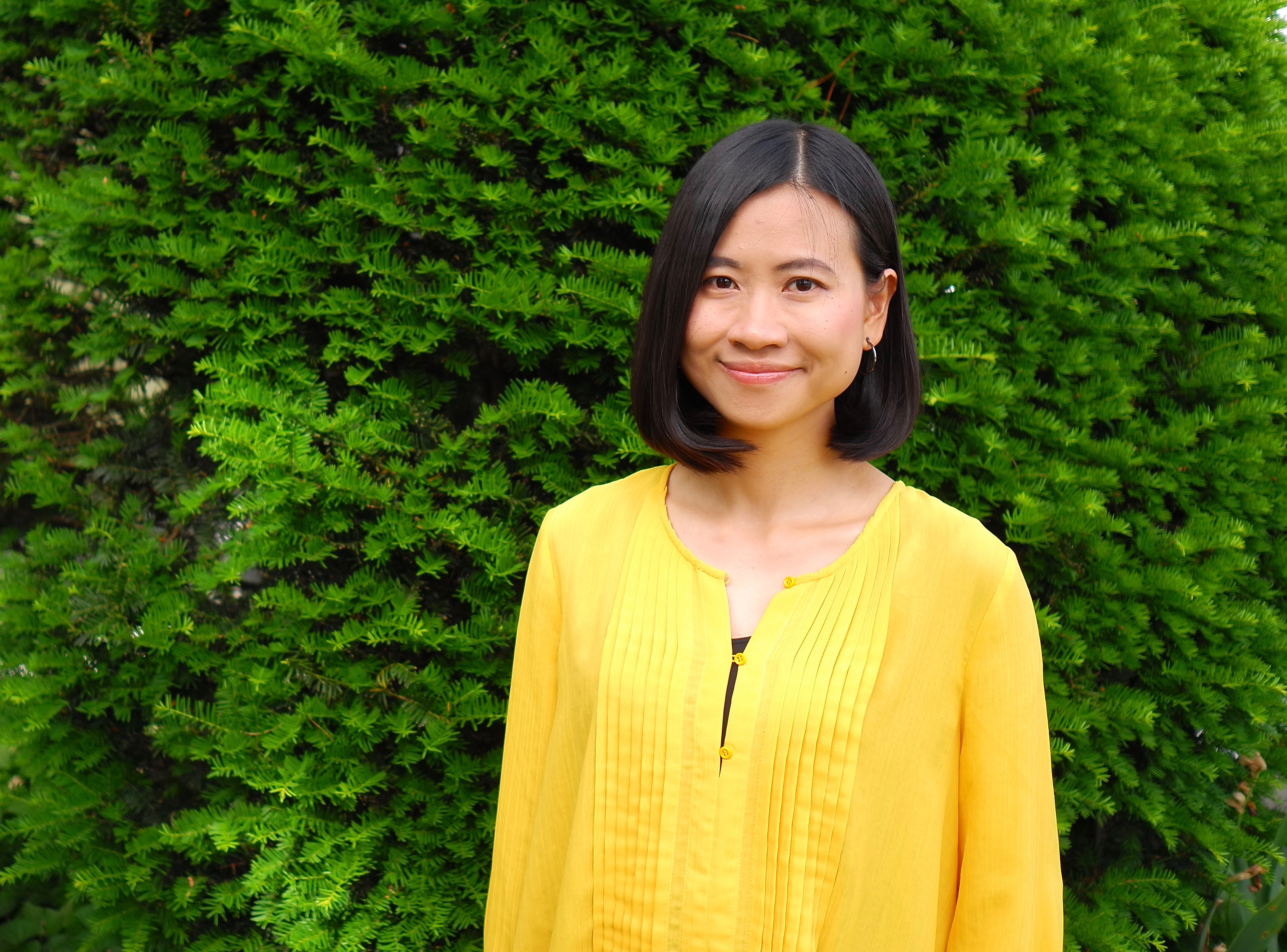 Graduate student Kongjing Xing wears a bright yellow shirt standing in front of a leafy, green tree