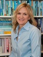 Penny Kittle standing in front of a shelf of books smiling
