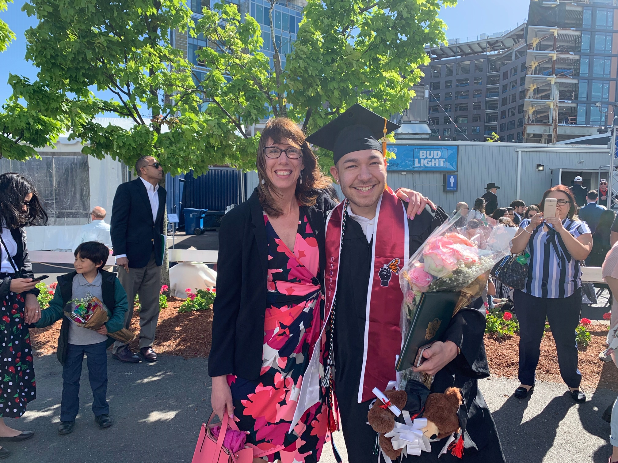 A woman and a young man in his graduation cap and gown posing for a photo on Lesley graduation day 2019.
