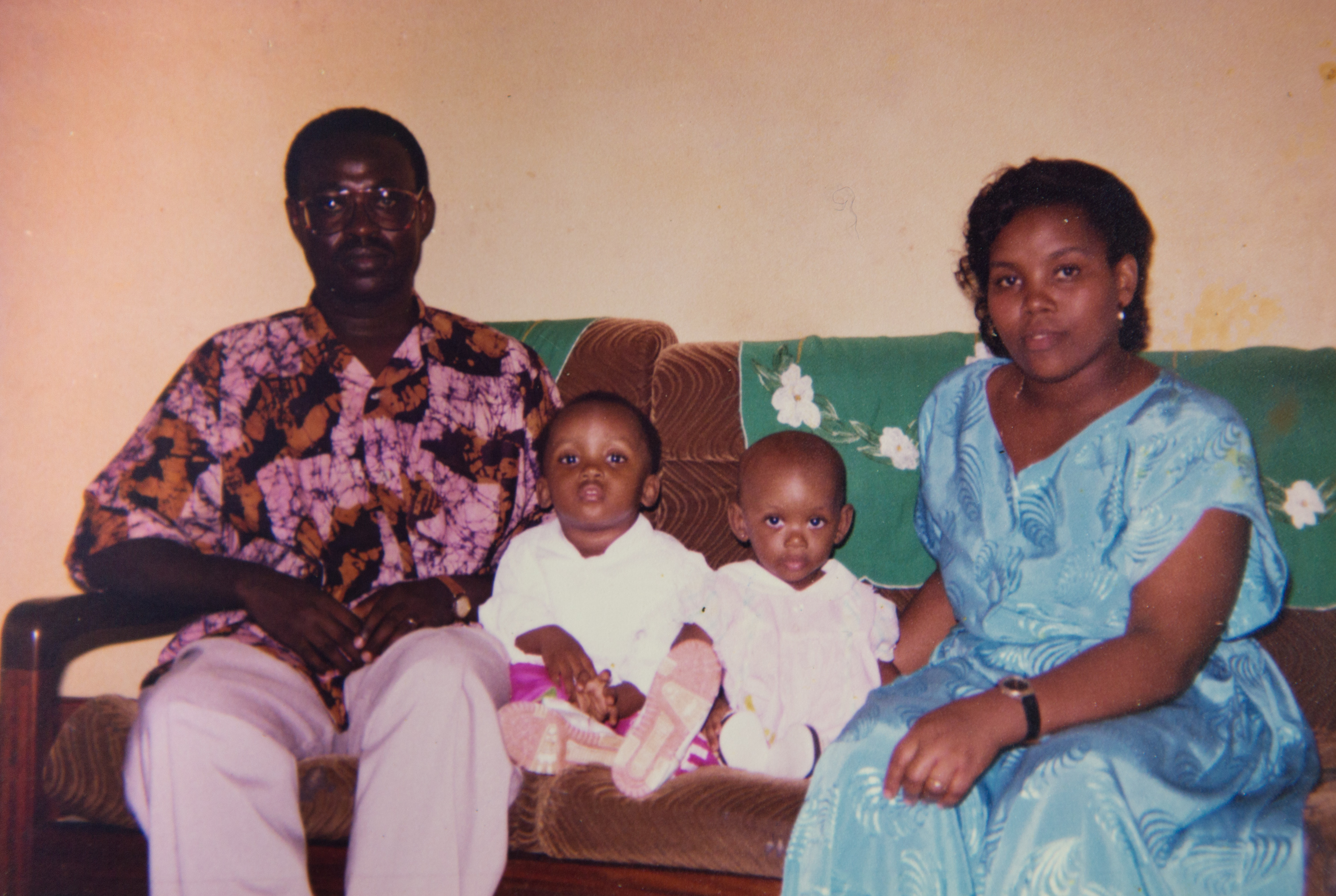 Marie Ntawizera, her husband and her two daughters sitting on a couch.