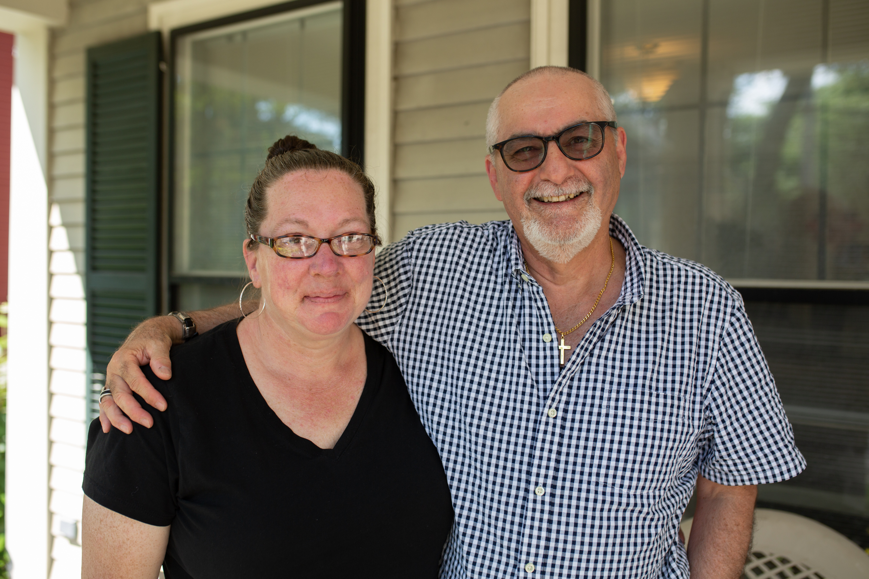 Gene Ferraro stands with his arm around Maryann Broxton on the front porch of the Center for the Adult Learner