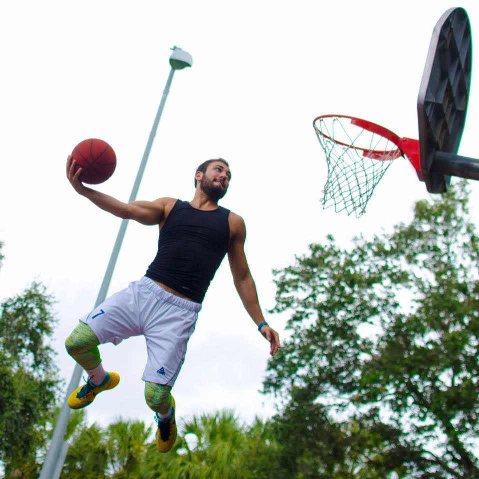 Shot from the ground up, Mike Kaufman jumps on a court with a ball in his hand.