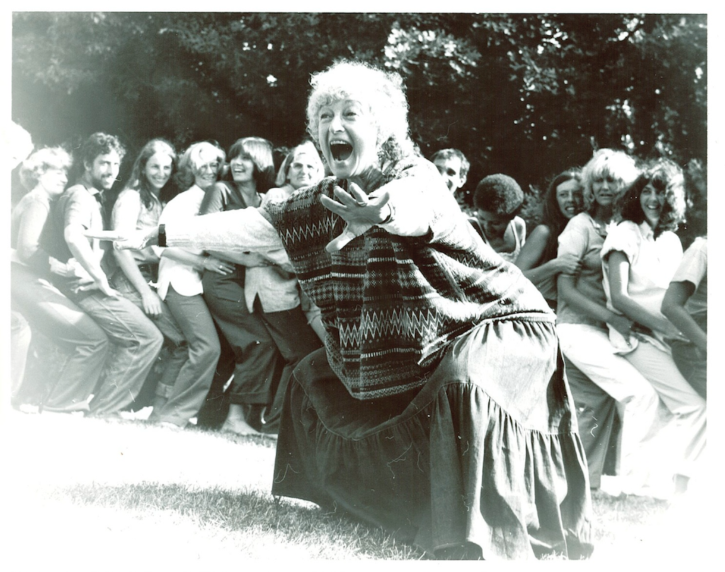 Black and white photo of woman dancing outside with line of dancers behind her.