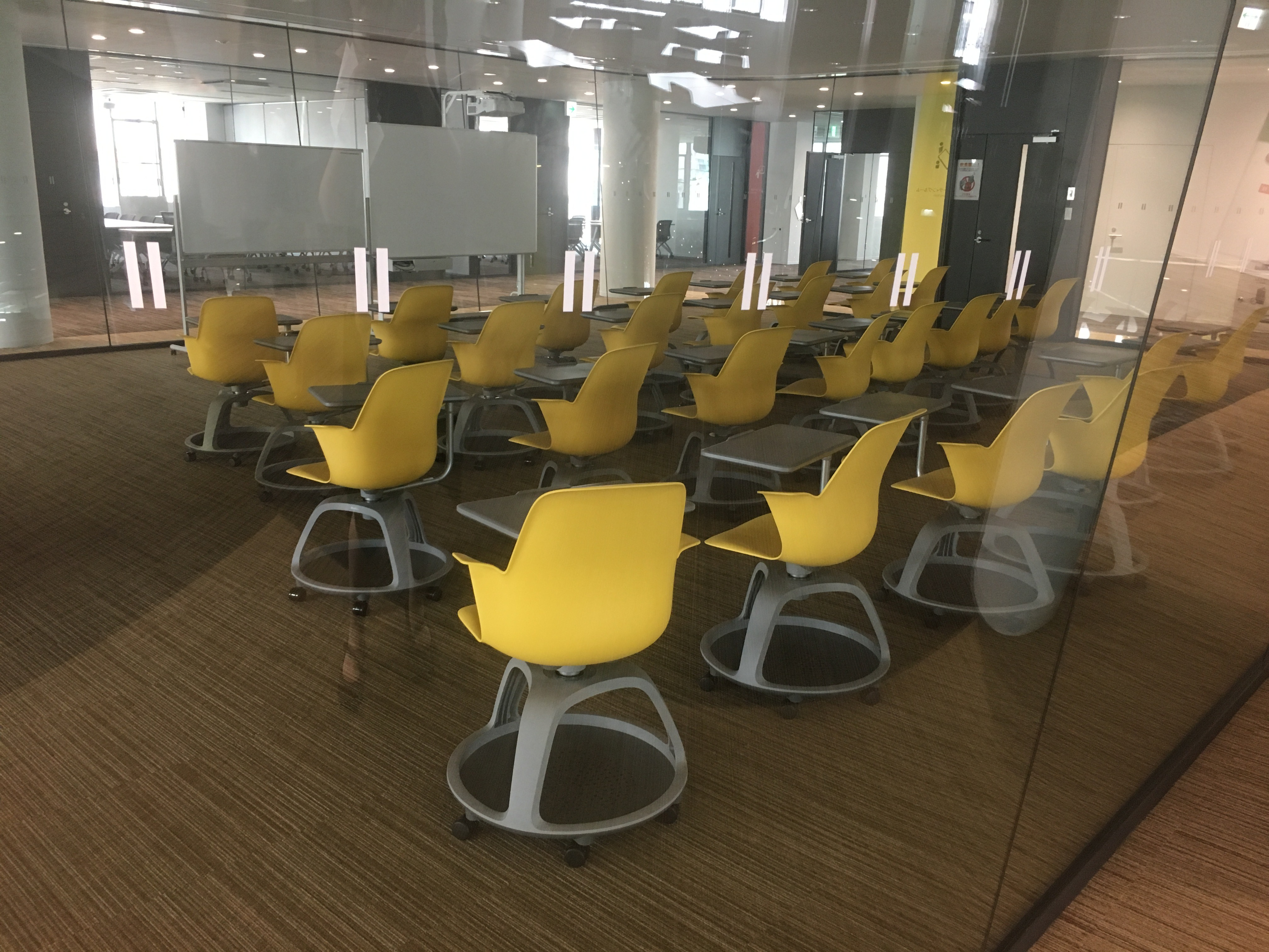 A classroom of yellow chairs that all have round trays attached underneath.