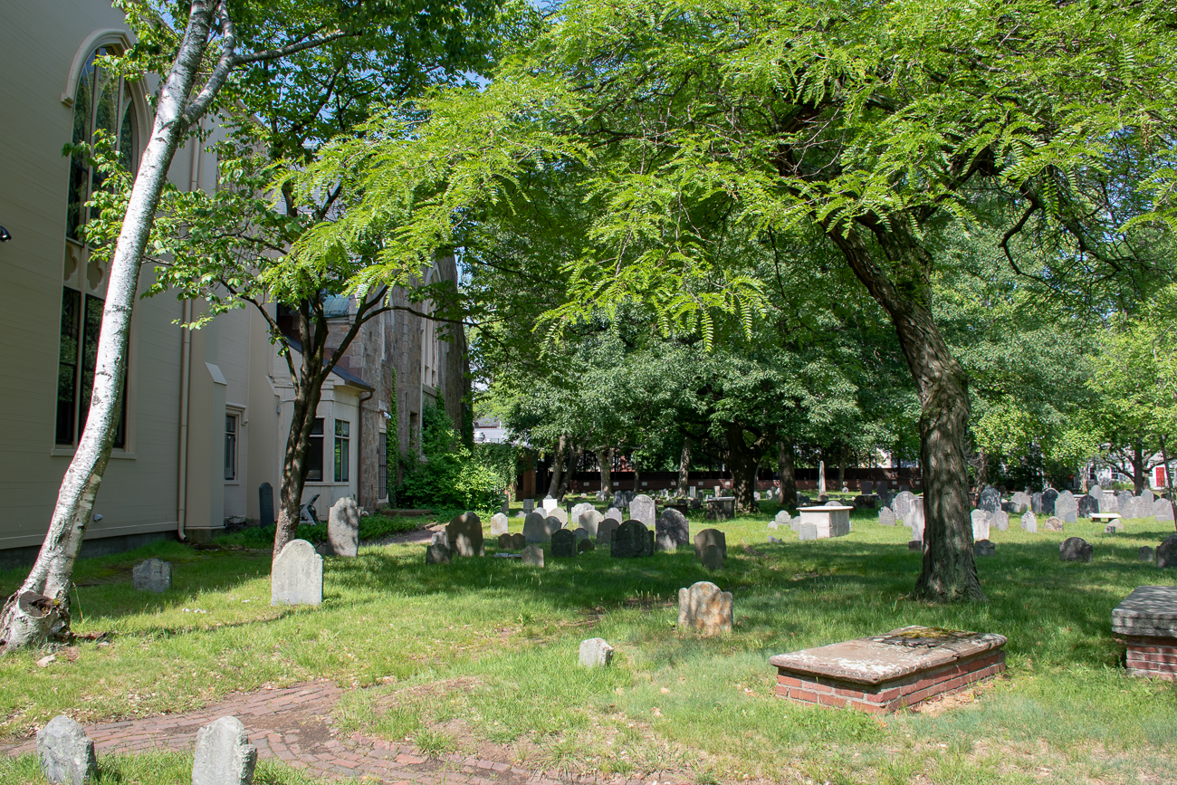 A view of graves and the side of the church next to the cemetery, with a lush tree casting shade.