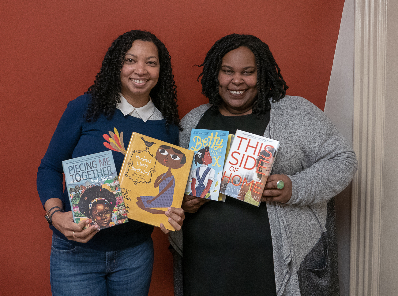 Tracey Baptiste and Renee Watson holding copies of Watson's books.