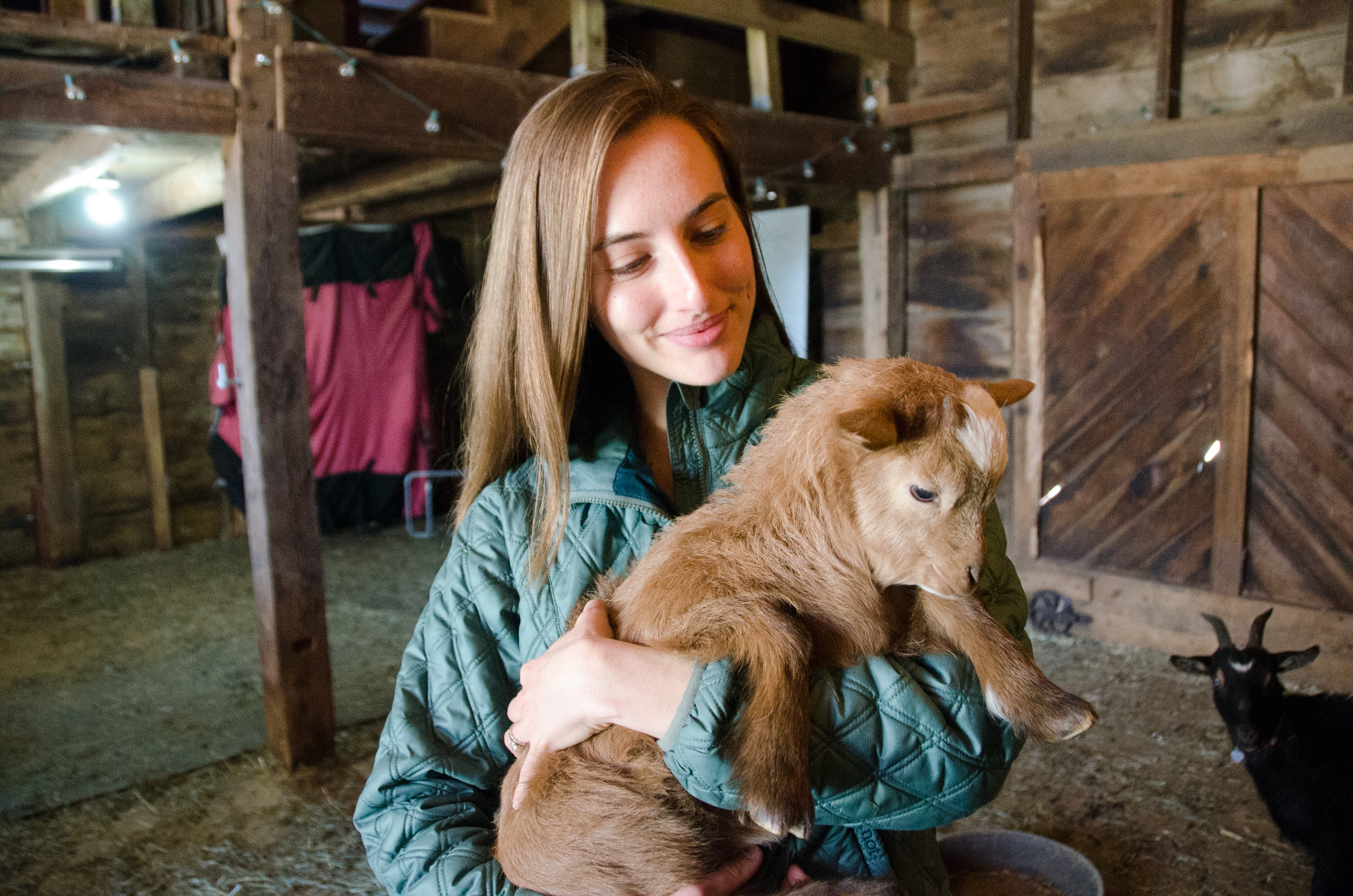 Samantha Sundermeyer with a baby goat at Cultivate Care Farm