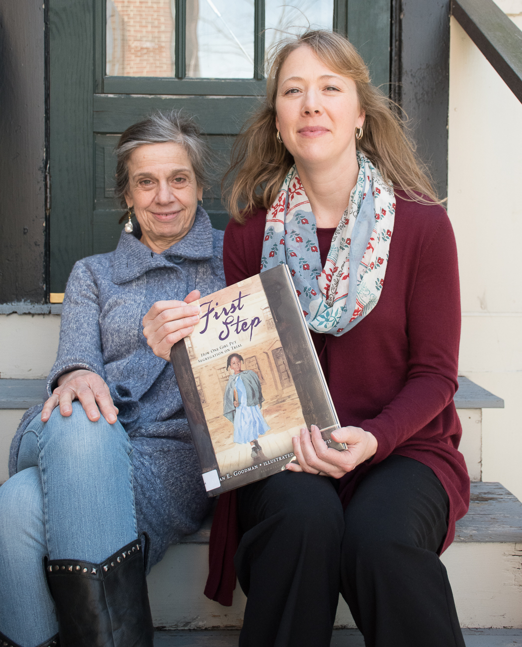 Susan Goodman and Erika Dawes sit on steps outside holding a copy of one of Susan's books