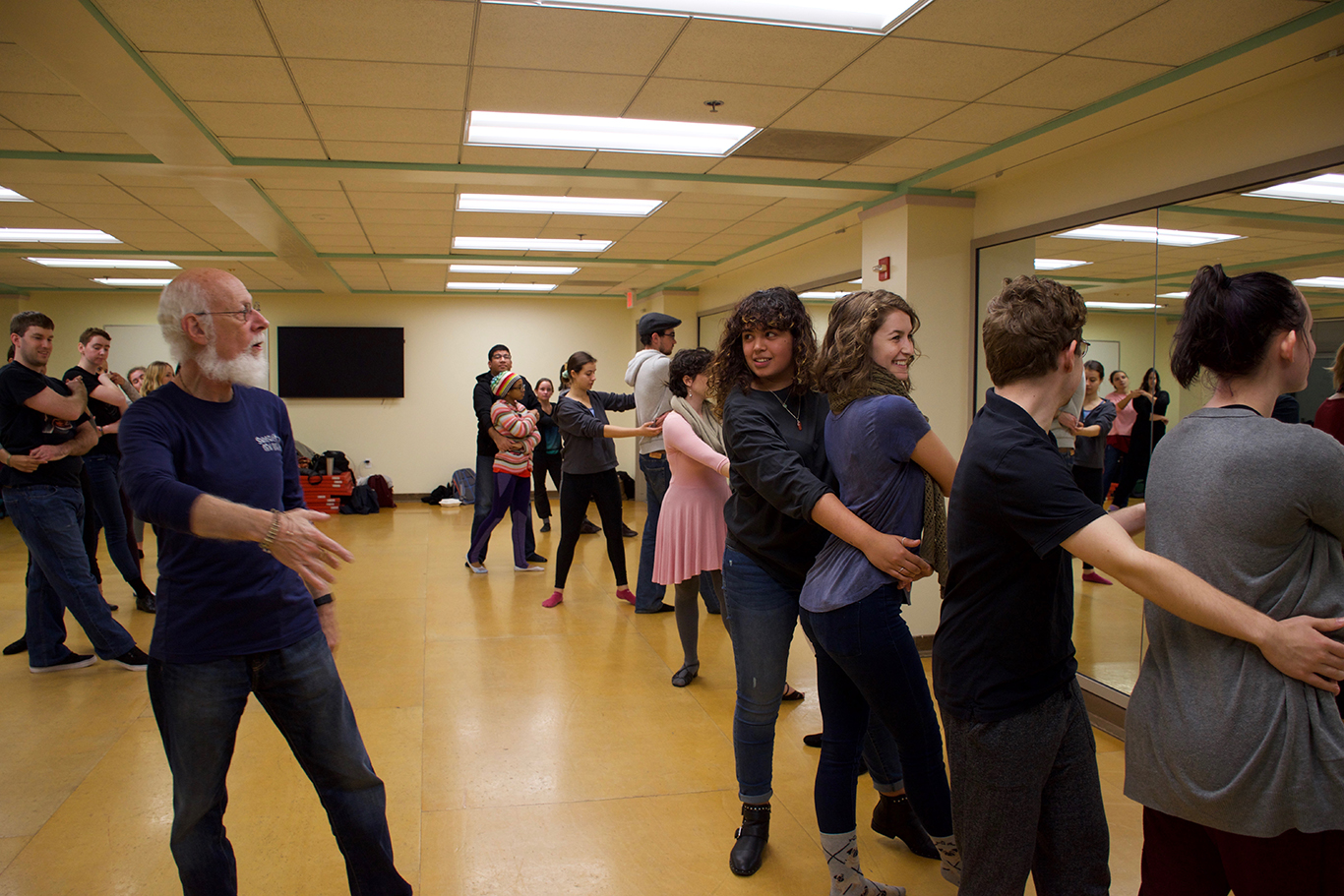 Professor shows students correct body placement during swing dance class in a dance studio.