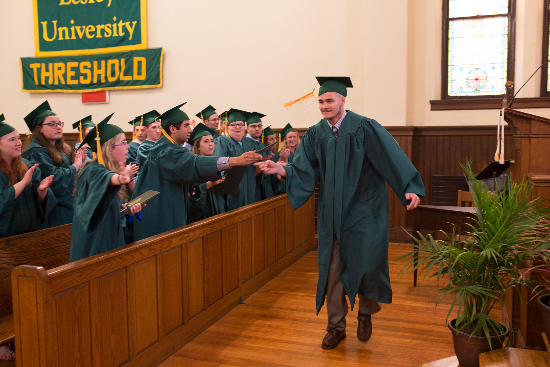 Graduate Chris Satterfield receives a high five as he approaches the stage.
