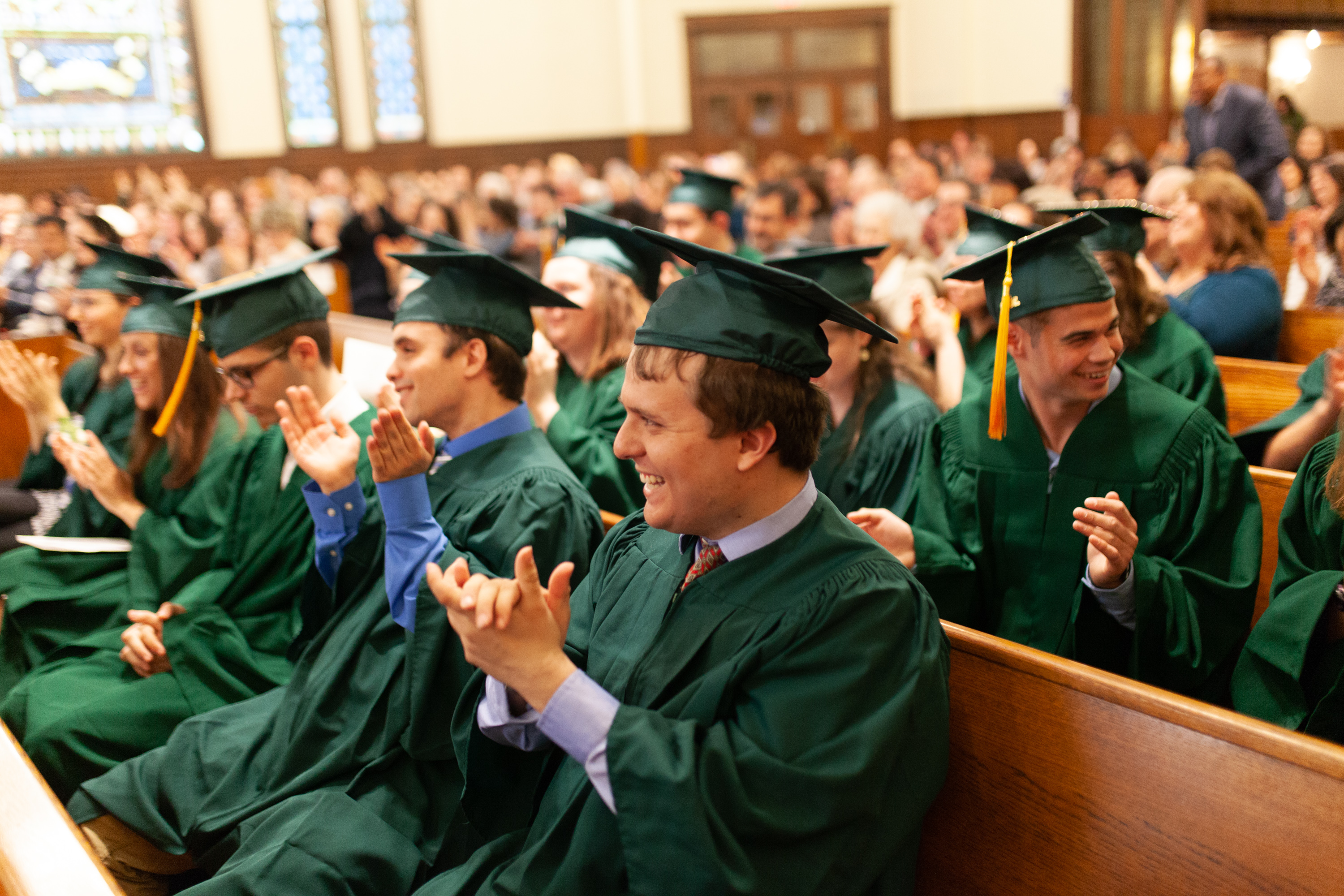 Graduates clap from the pews