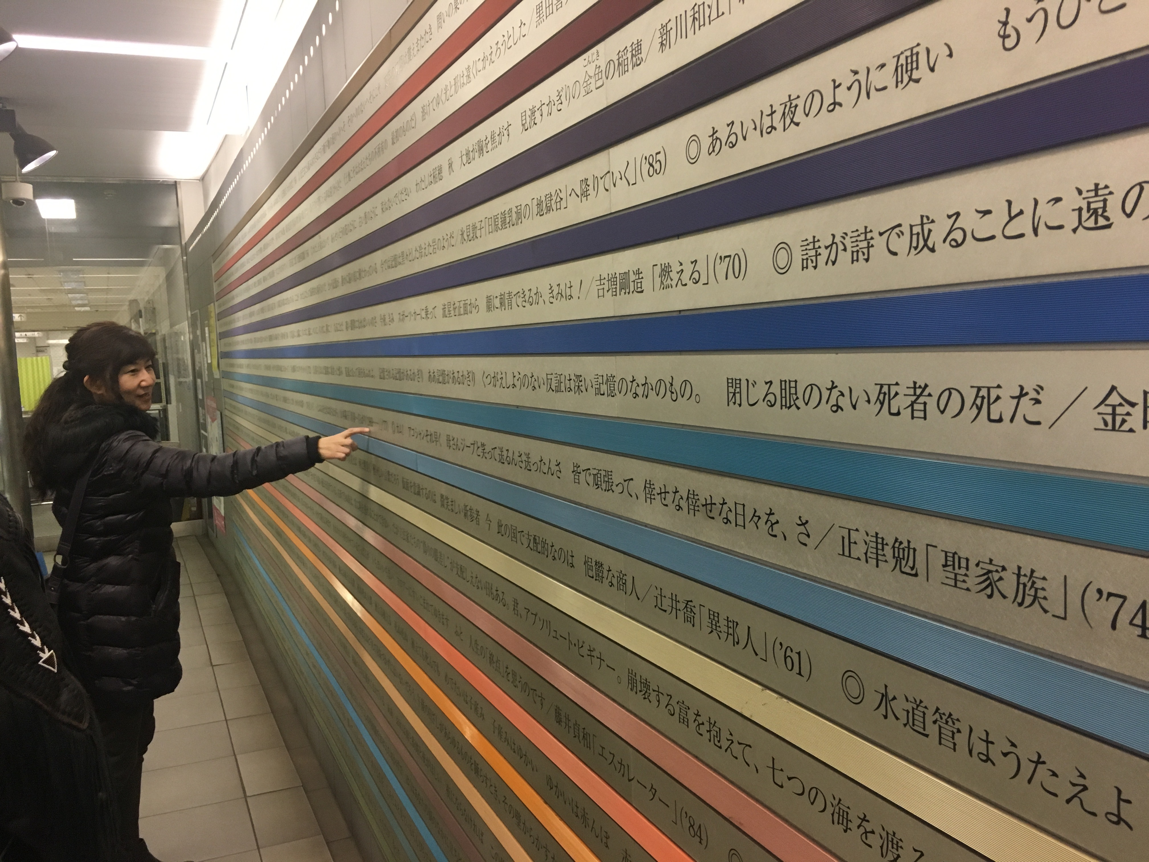 Professor Kazuyo Kubo looks at poetry printed on the walls of a subway station. Between each line is a band of color.