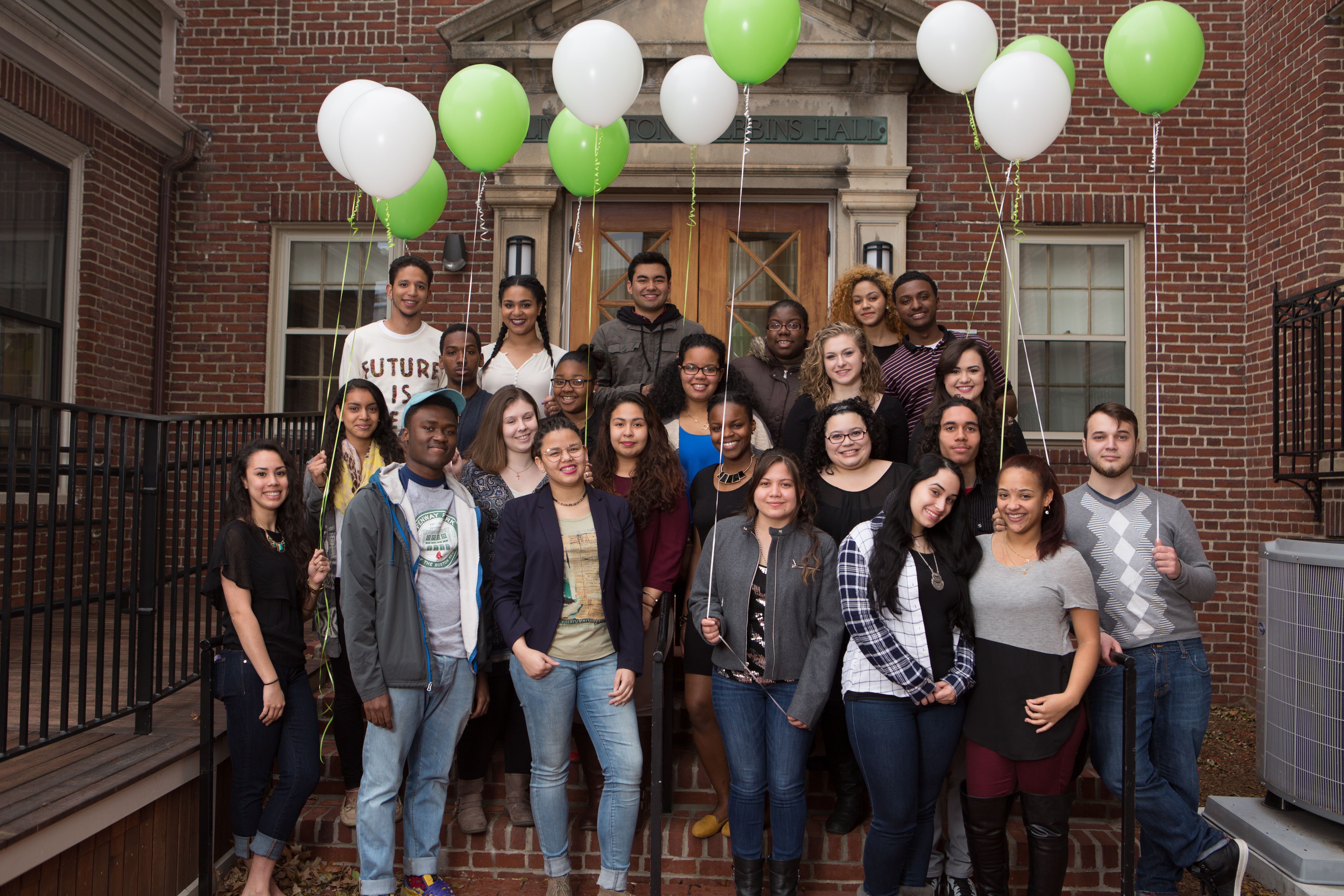 The USI students as freshmen standing outside Alumni Hall with green and white balloons.