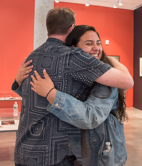Standing in the art gallery, Vaughan Oliver hugs a female student who has a smile on her face.