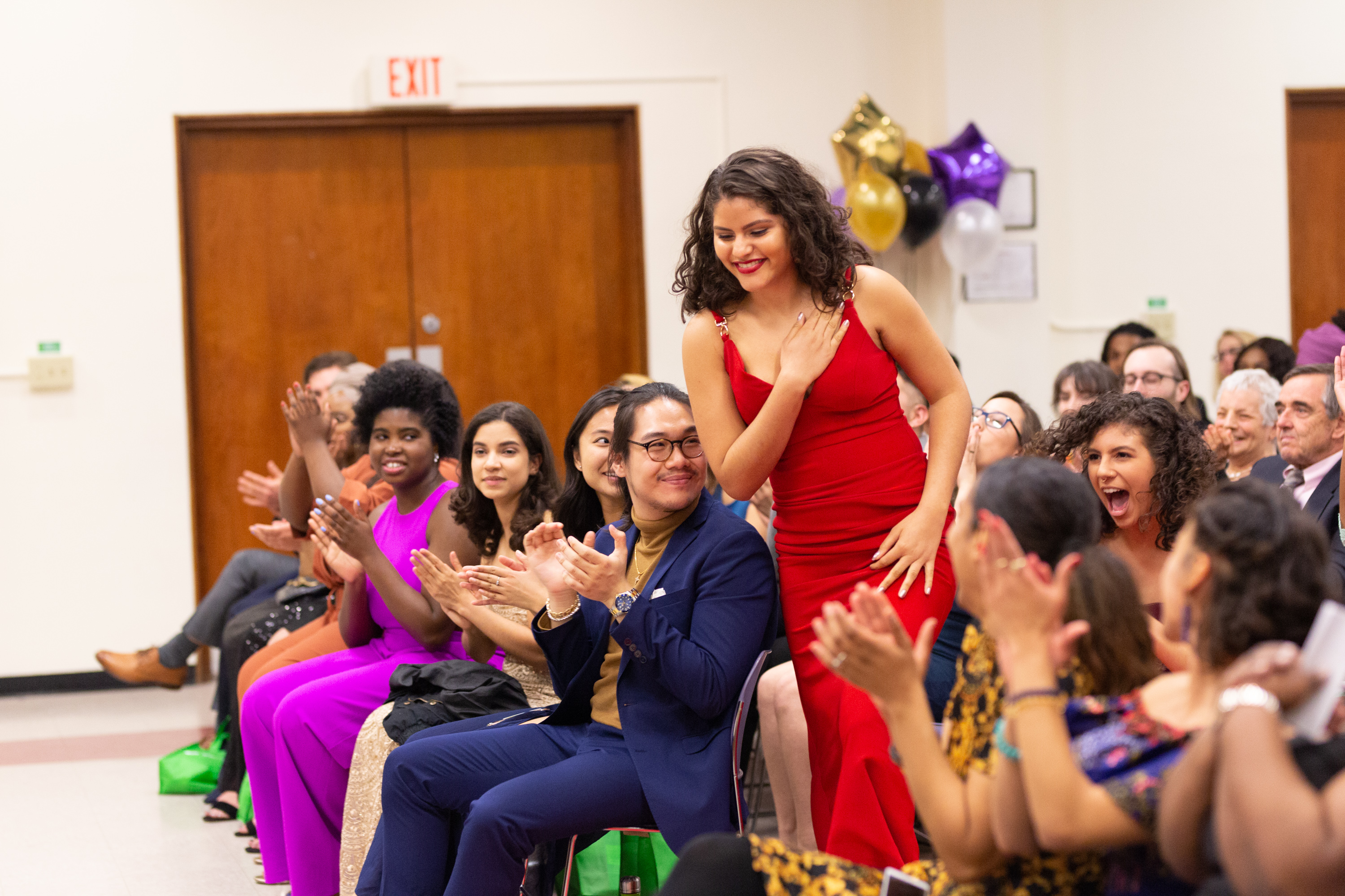 Woman in a red gown stepping out of the audience to receive an award at the Unity Gala.