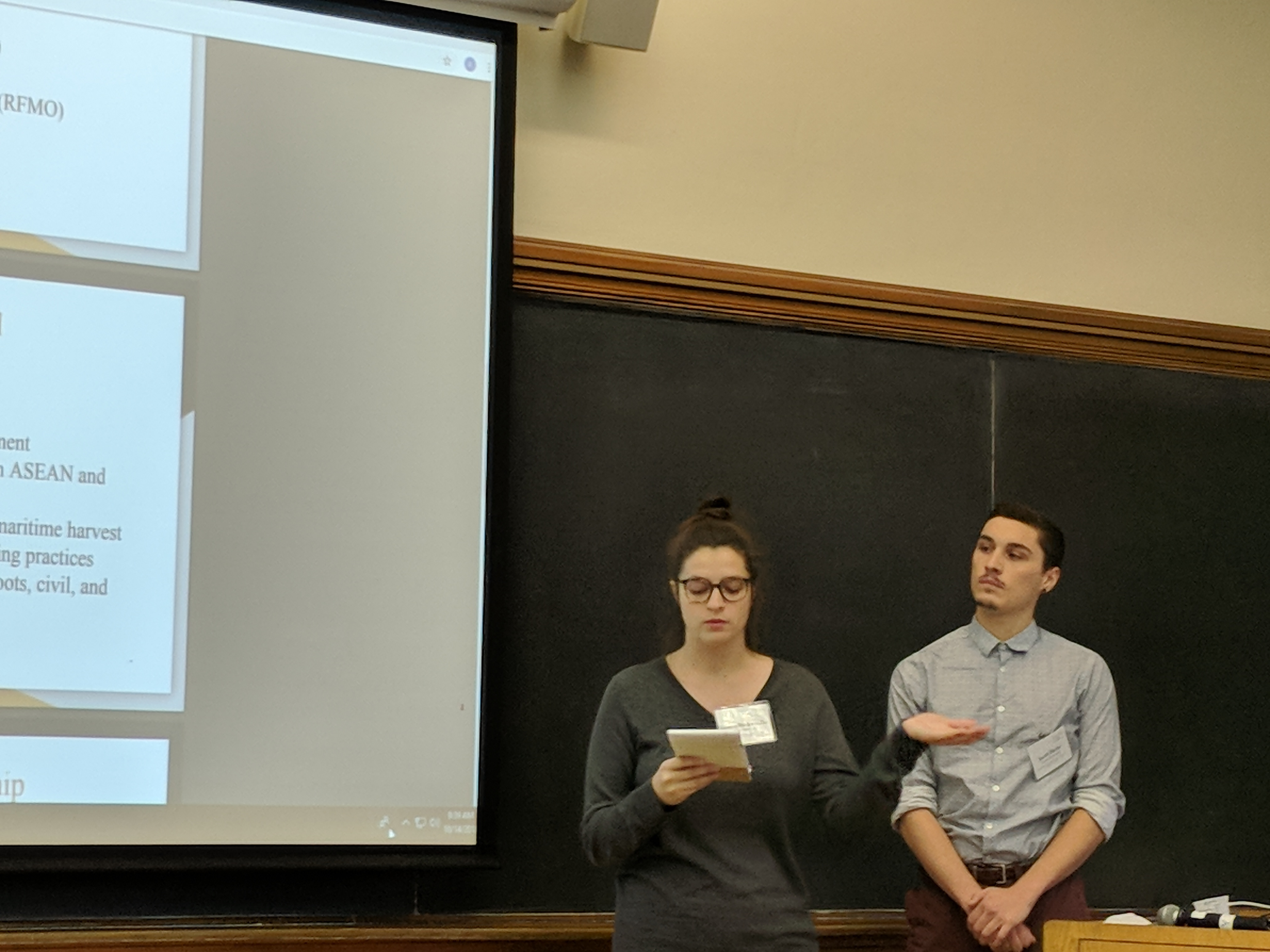 Students Kolette Bodenmiller and Jacob Hicks stand in front of a blackboard at Yale and present during the policy competition