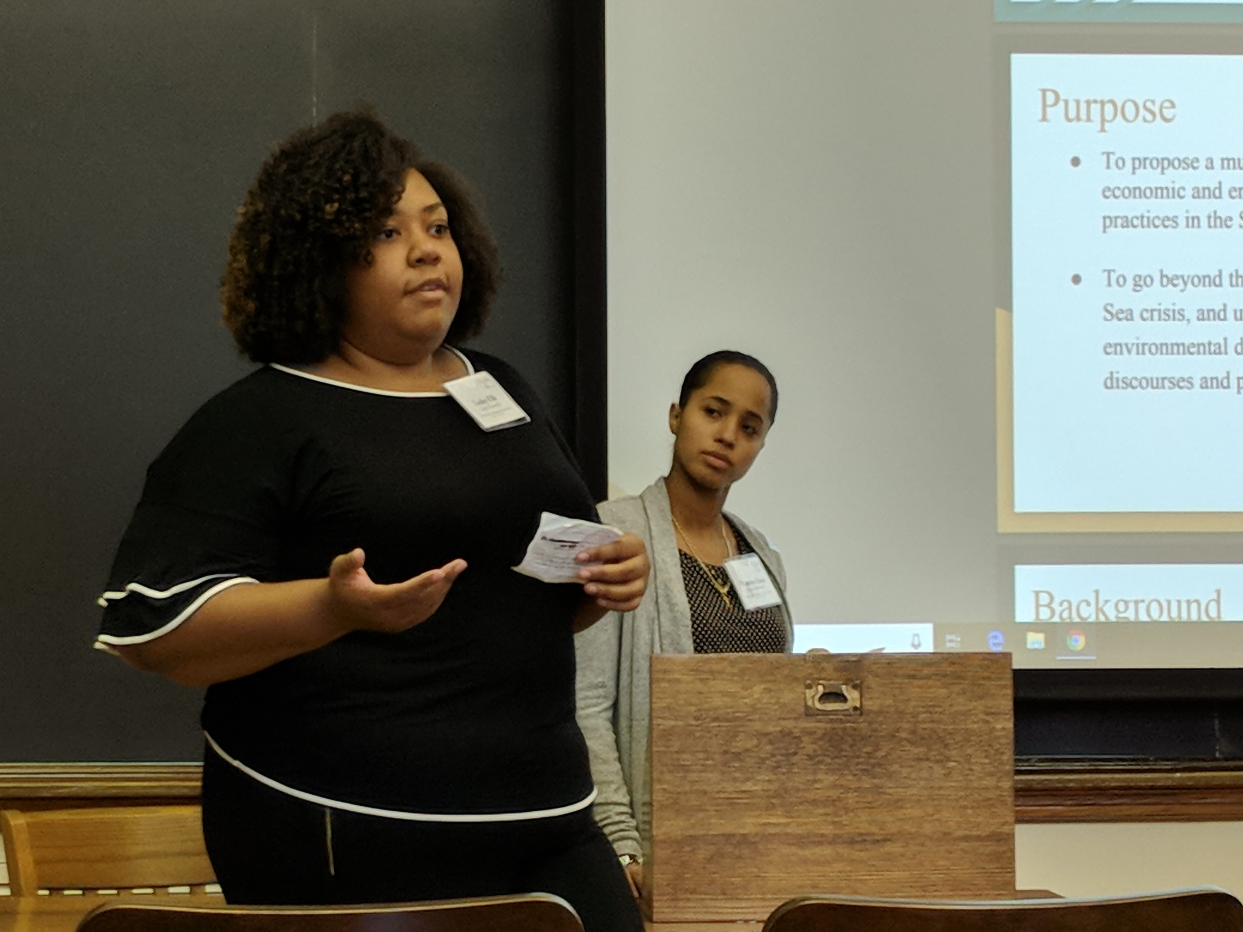 Students Lesley Ells and Tamara Grant deliver a presentation in front of a PowerPoint at the Yale Policy Competition