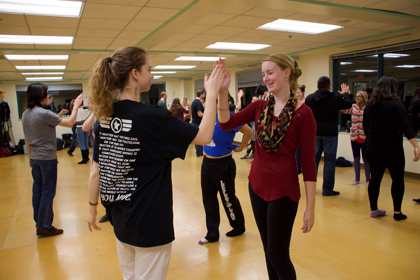Students high-five each other in a dance studio during dance class.