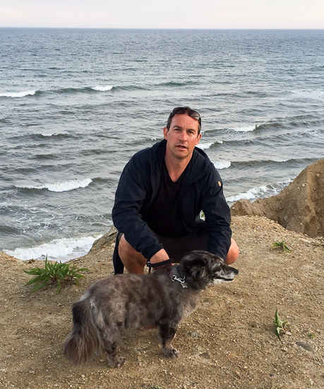 Scott Loring Sanders photographed on the beach with his dog.