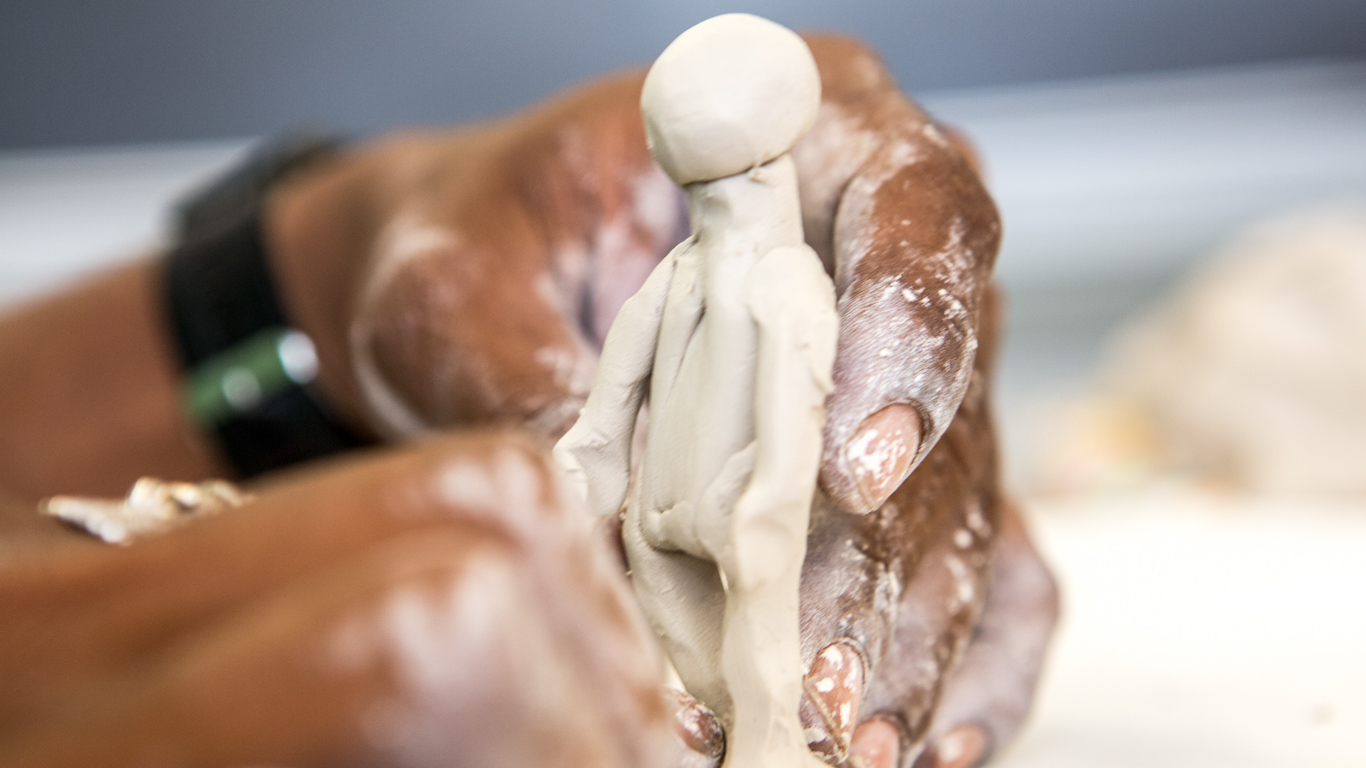 A close up of a persons hands molding a small figurine of a person