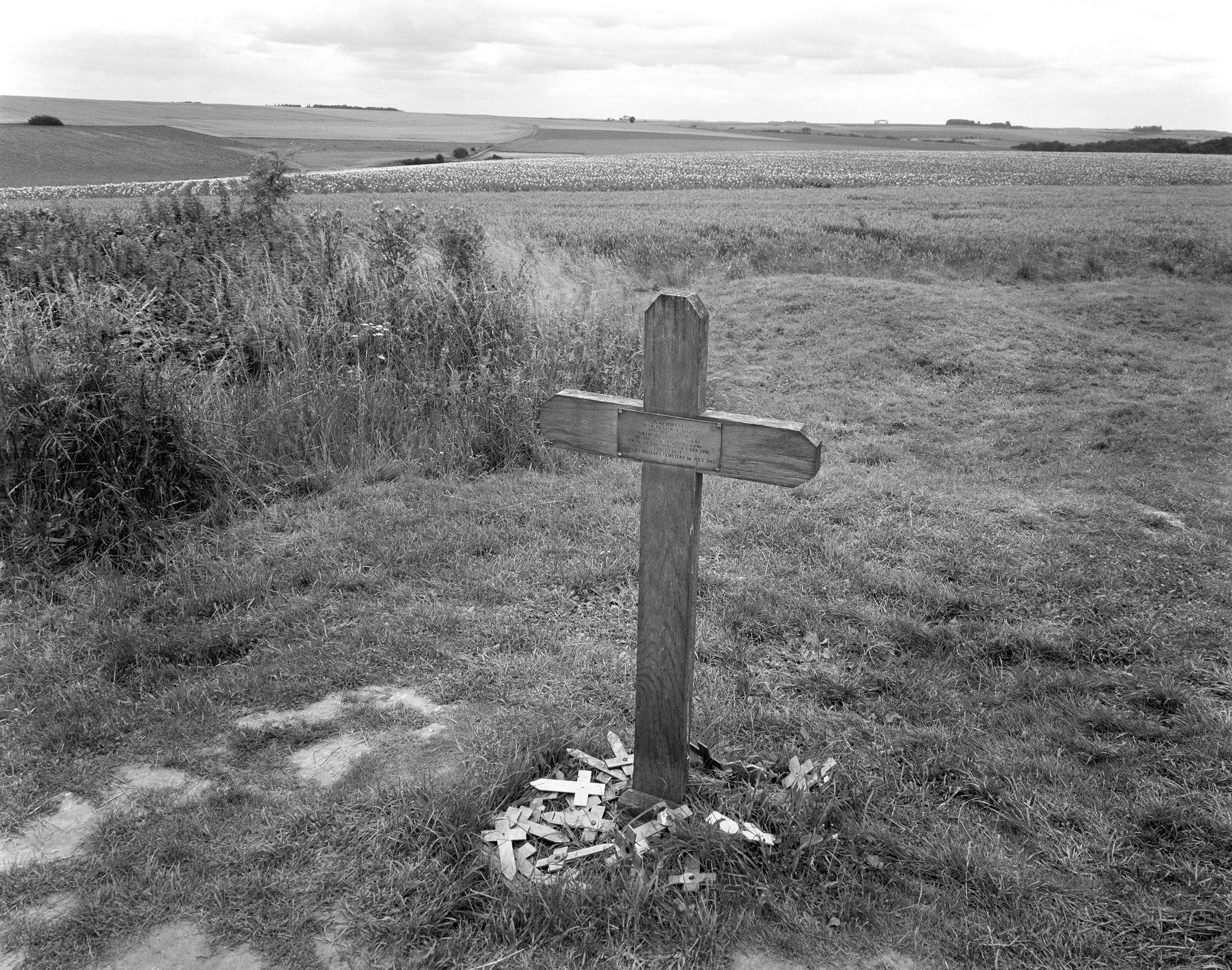 black and white photo of field with cross marking someone's grave