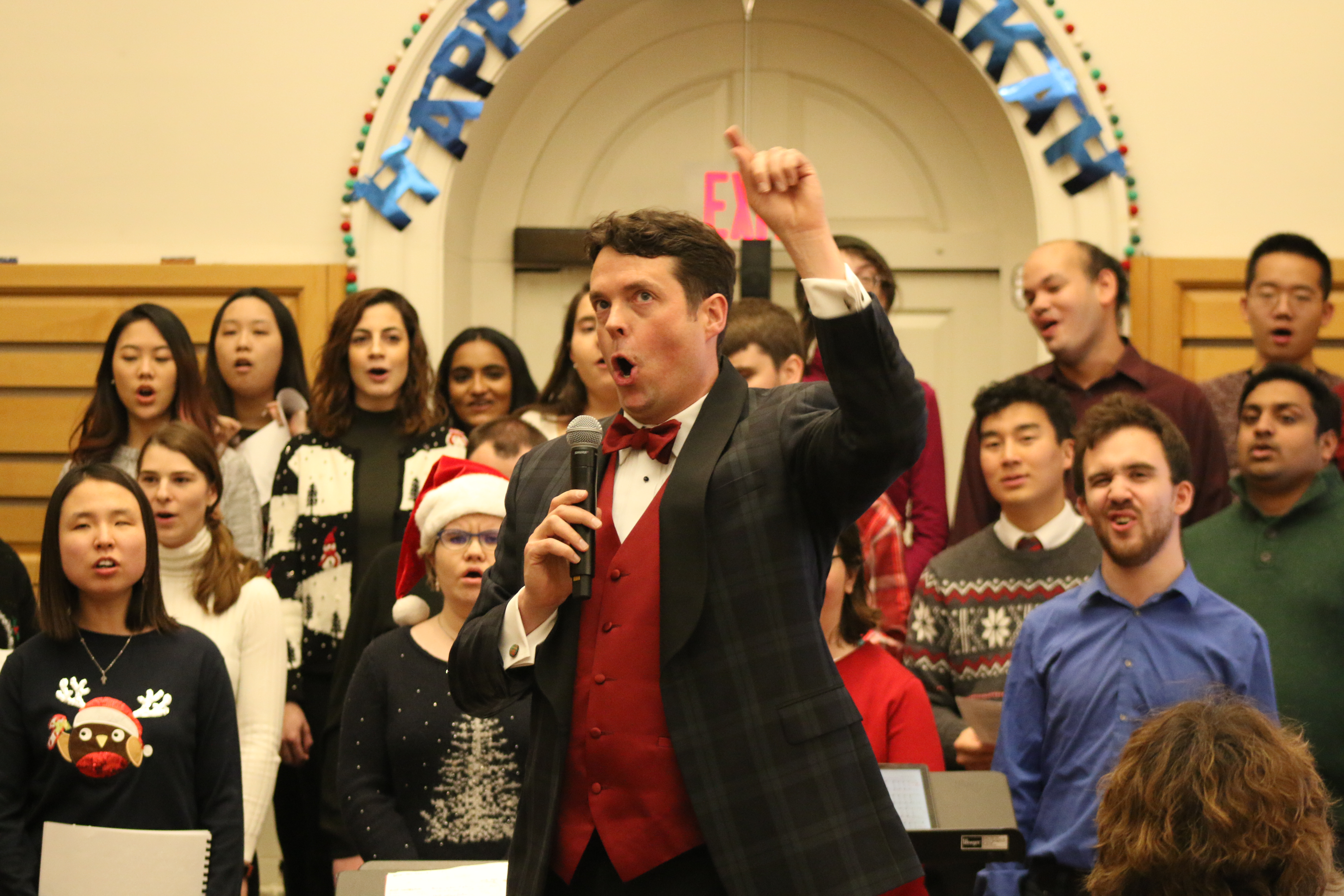 A man (the choir director) sings with hand raised at the holiday concert