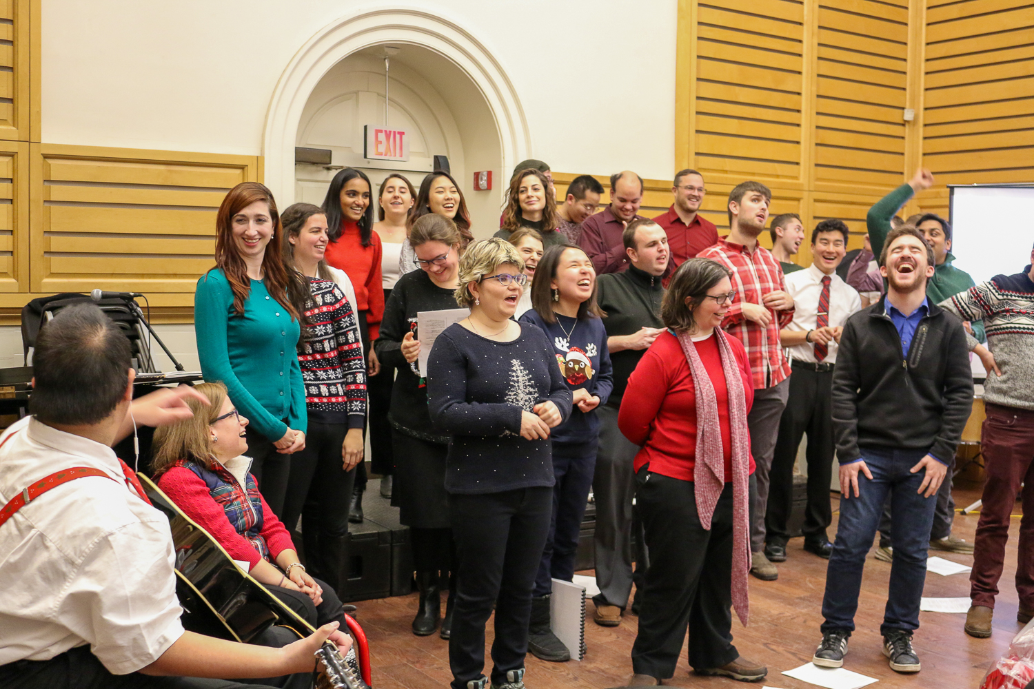Choir wearing holiday sweaters and singing