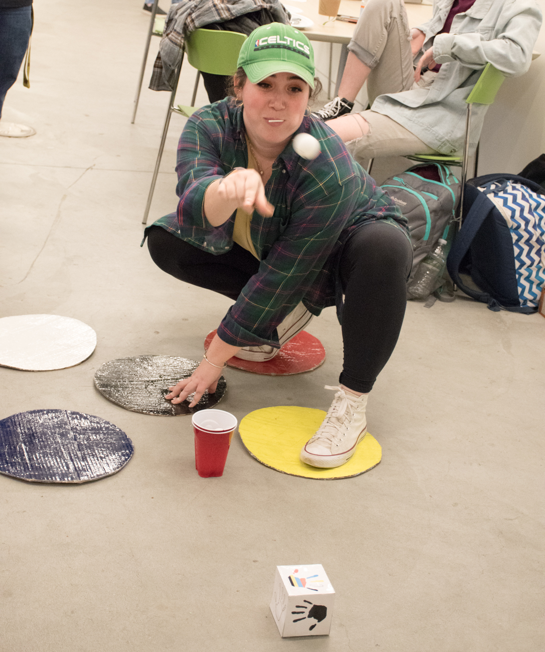 A girl crouches down on several colored Twister cirlces and throws a ball.